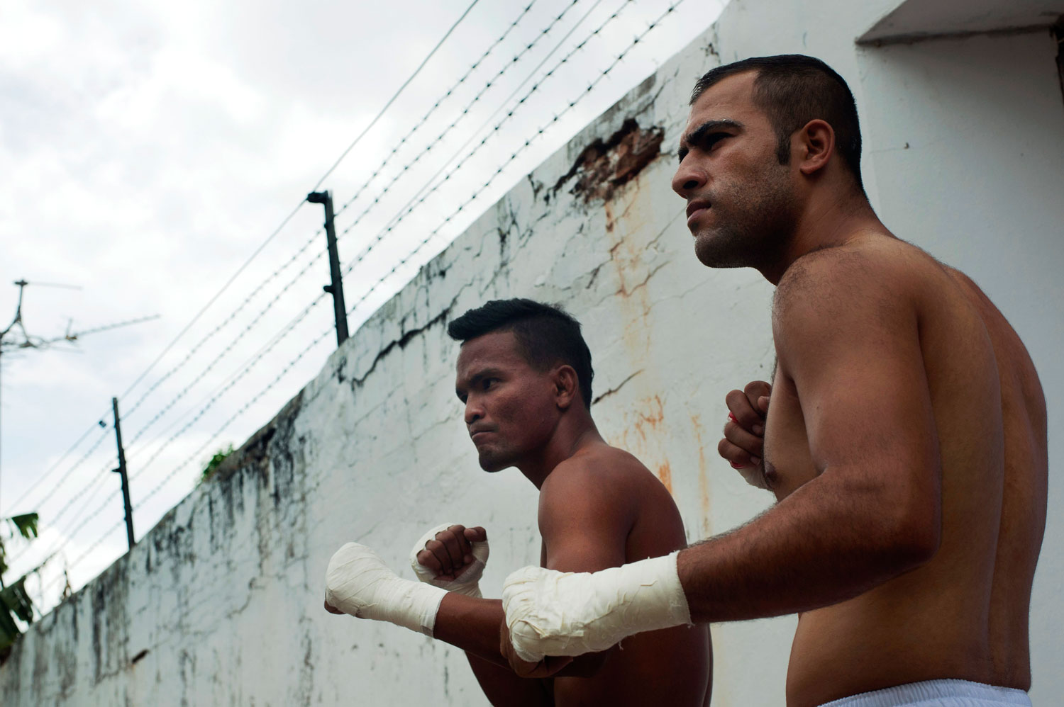 An inmate and a foreign fighter pose before their fight at Klong Pai prison on July 12, 2014 in Nakhon Ratchasima, Thailand.