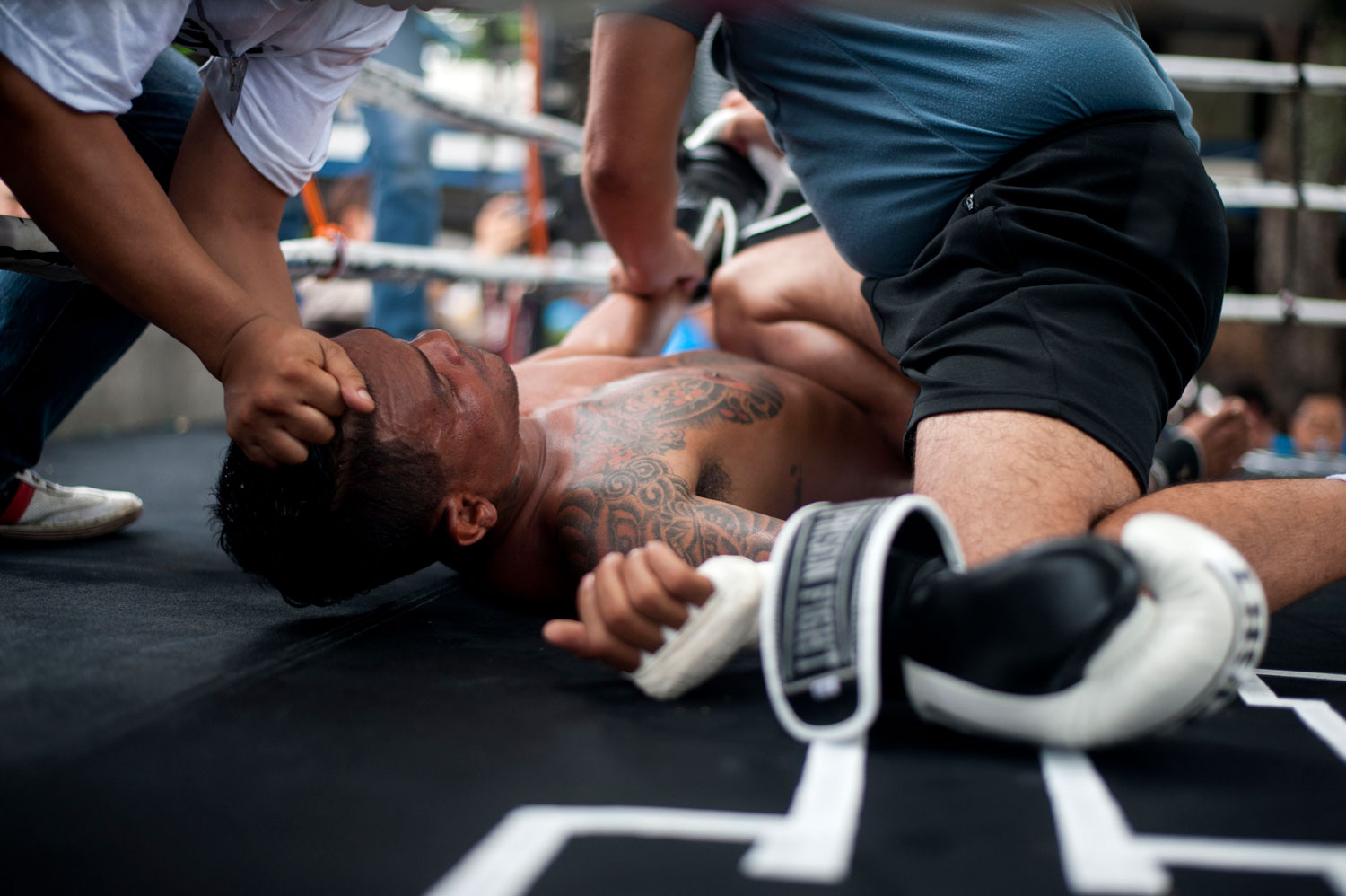 An inmate is helped after he falls to the floor during a Muay Thai fight at Klong Pai prison on July 12, 2014 in Nakhon Ratchasima, Thailand.