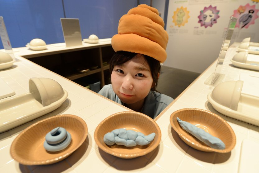 A staff member wearing a poo-shaped hat poses at a toilet exhibition at the National Museum of Emerging Science and Innovation in Tokyo on July 9, 2014.