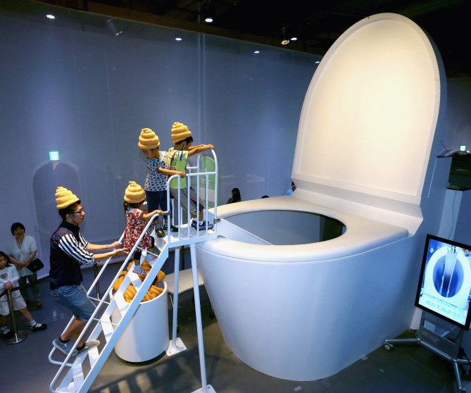 Children play at the 5-meter-tall toilet shaped slider during the 'Toilet!? Human Waste and Earth's Future' exhibition at The National Museum of Emerging Science and Innovation - Miraikan on July 5, 2014 in Tokyo.