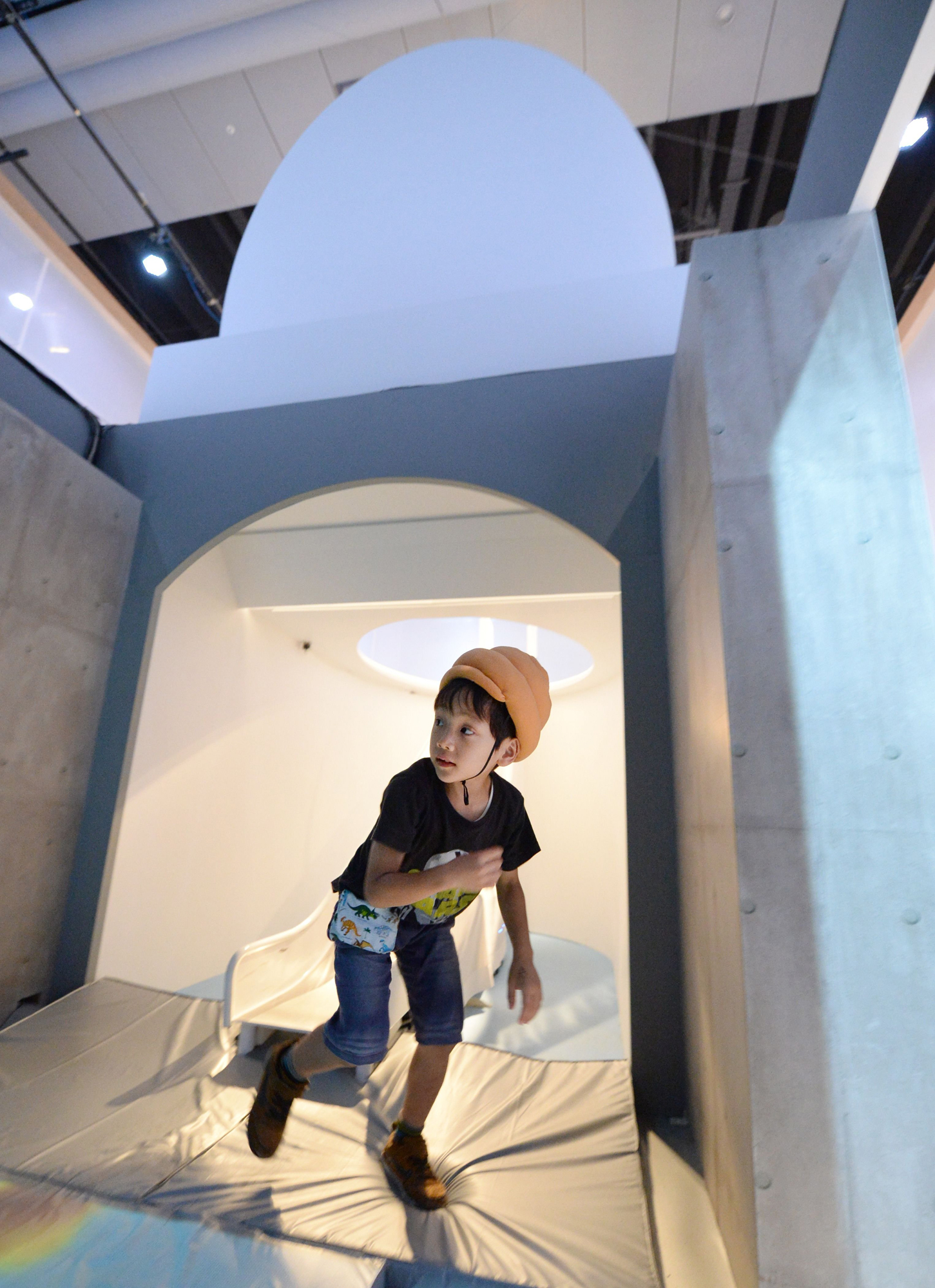 A child wearing a poo-shaped hat gets up from a giant toilet slide at a toilet exhibition at the National Museum of Emerging Science and Innovation in Tokyo on July 9, 2014.