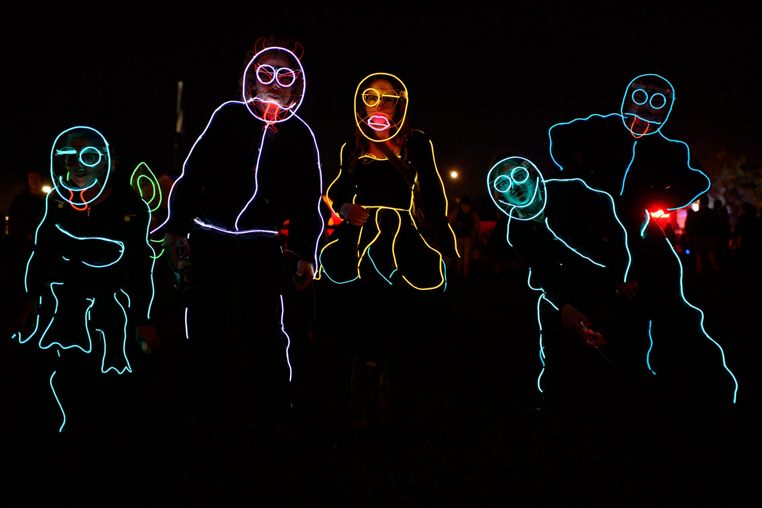 People wear neon body outlines as they walk through the site, on the second day of the Glastonbury Festival of Music and Performing Arts in Somerset, southwest England, on June 28, 2014.