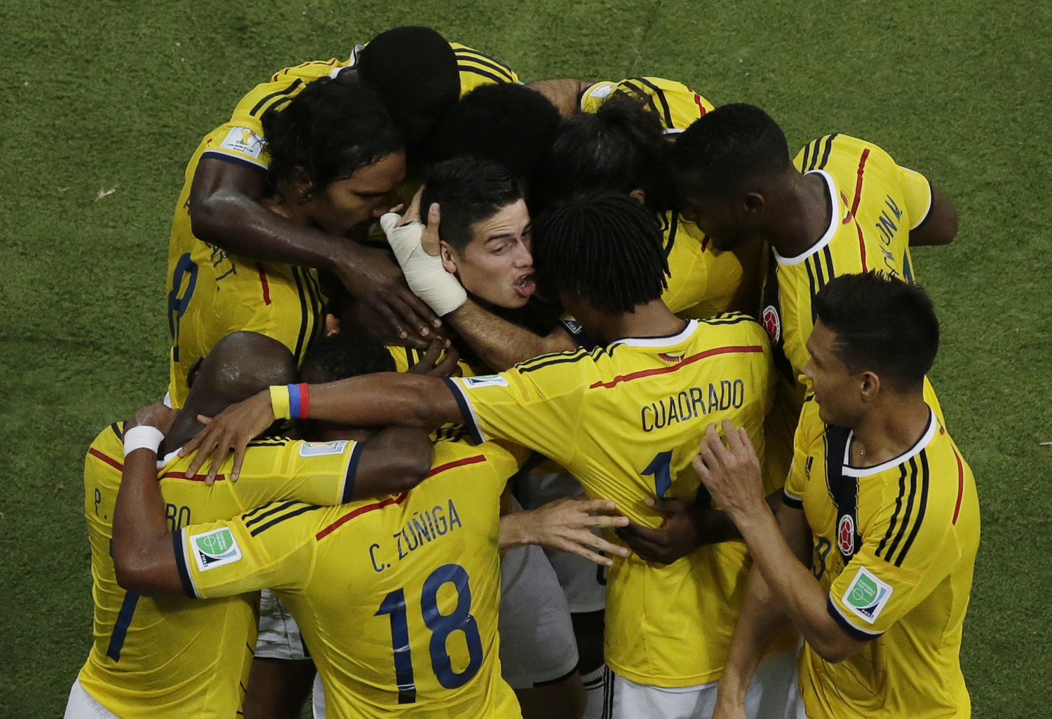Colombia's midfielder James Rodriguez (C) is mobbed by teammates as he celebrates scoring a goal during the Round of 16 football match between Colombia and Uruguay at The Maracana Stadium in Rio de Janeiro on June 28, 2014.