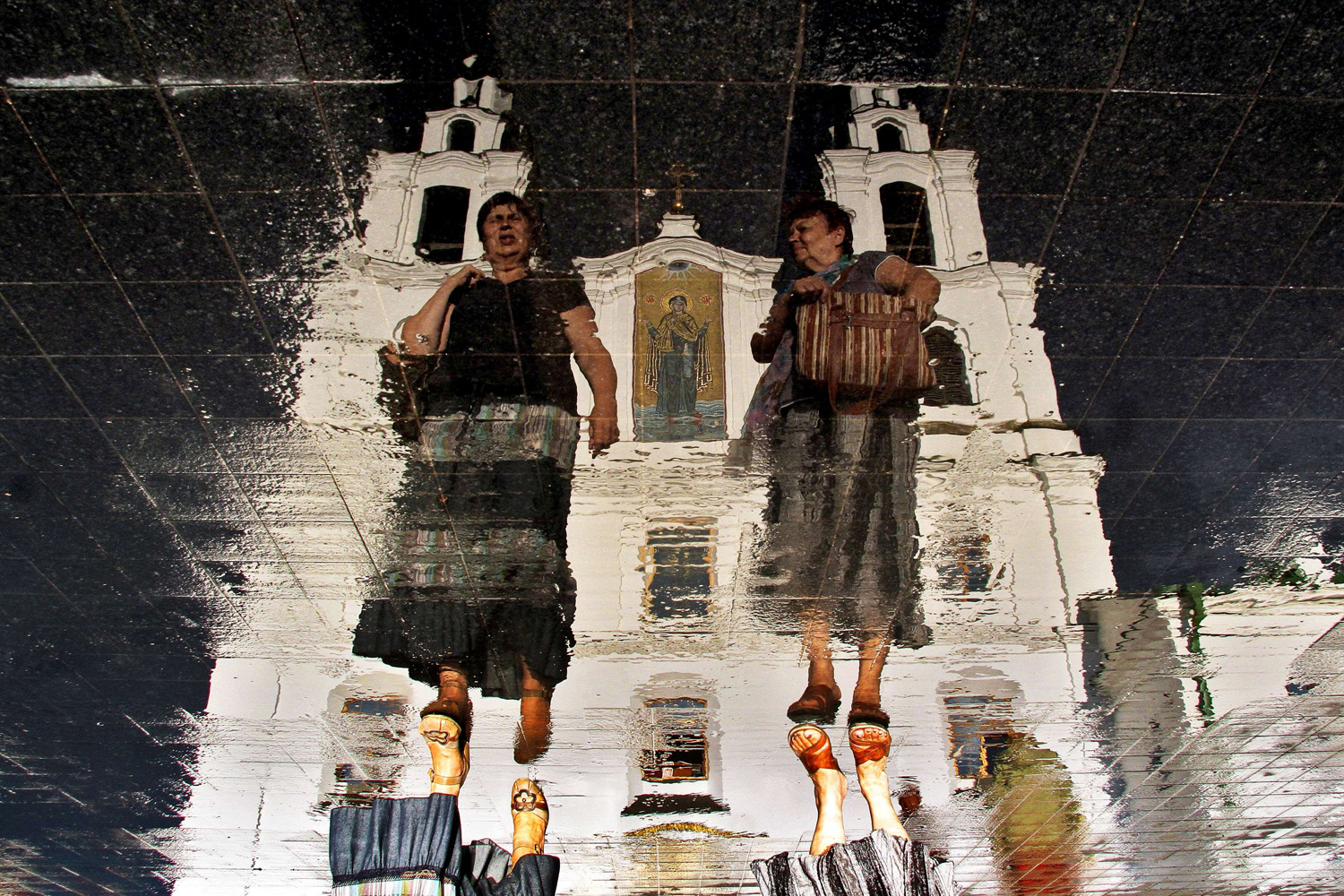 Jul. 20, 2014. Two women walking in front of  Svyato-Dukhov (Holy Spirit ) Orthodox cathedral  are reflected in the wet tablets of a roadway in the Belarus capital Minsk.