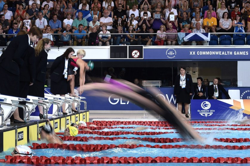 Swimmers dive in during the Women's 4 x 200m Freestyle Relay Final at the Tollcross International Swimming Centre during the 2014 Commonwealth Games in Glasgow on July 26, 2014.