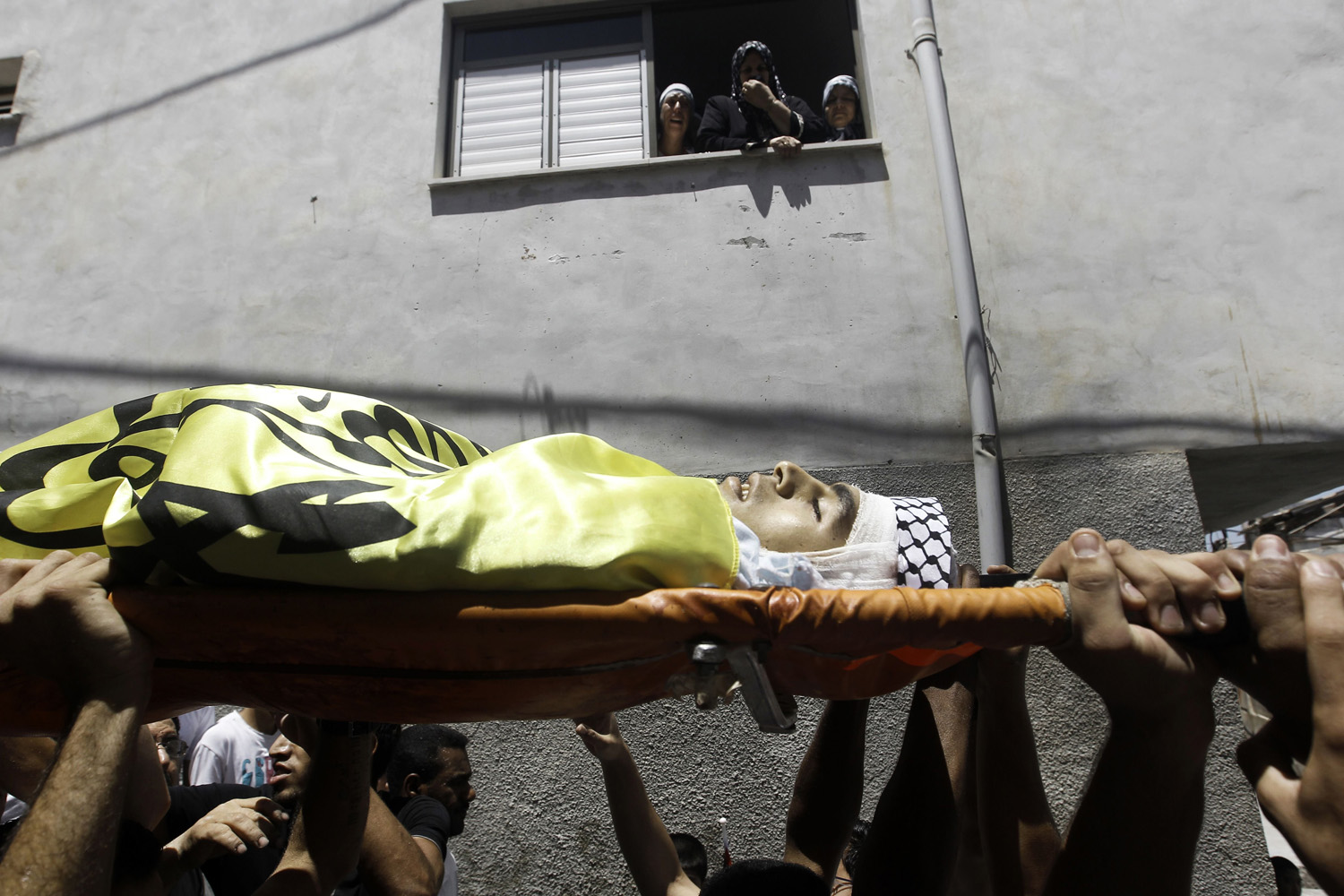Jul. 1, 2014. Palestinian mourners carry the body of Yusuf Abu Zagher, 18, during his funeral in the Jenin refugee camp, in the northern Israeli occupied West Bank.