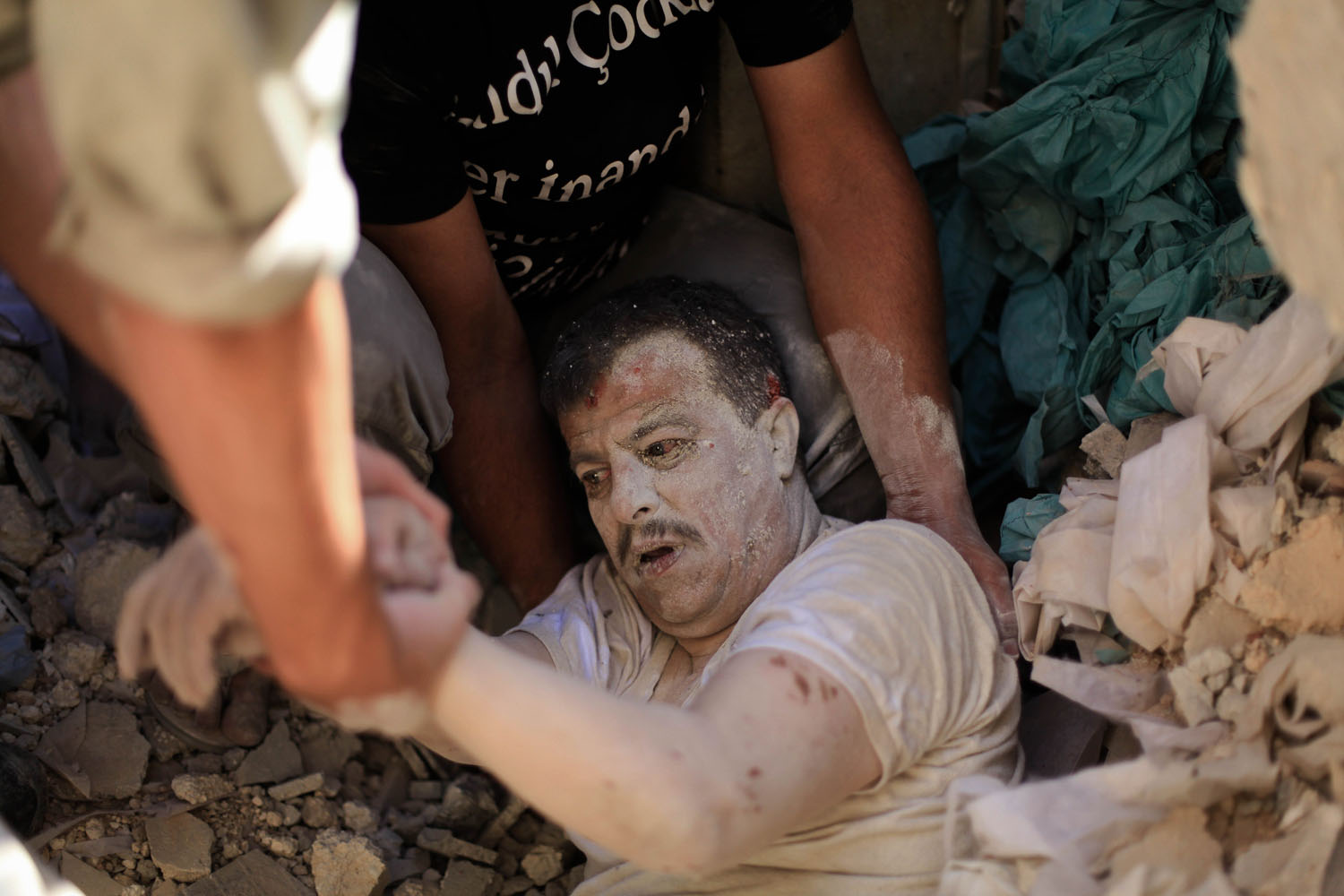 Jul. 7, 2014. Members of the Syrian Civil Defence rescue a man under the rubble following a reported barrel-bomb attack by Syrian government forces in the Qadi Askar neighbourhood in Aleppo.