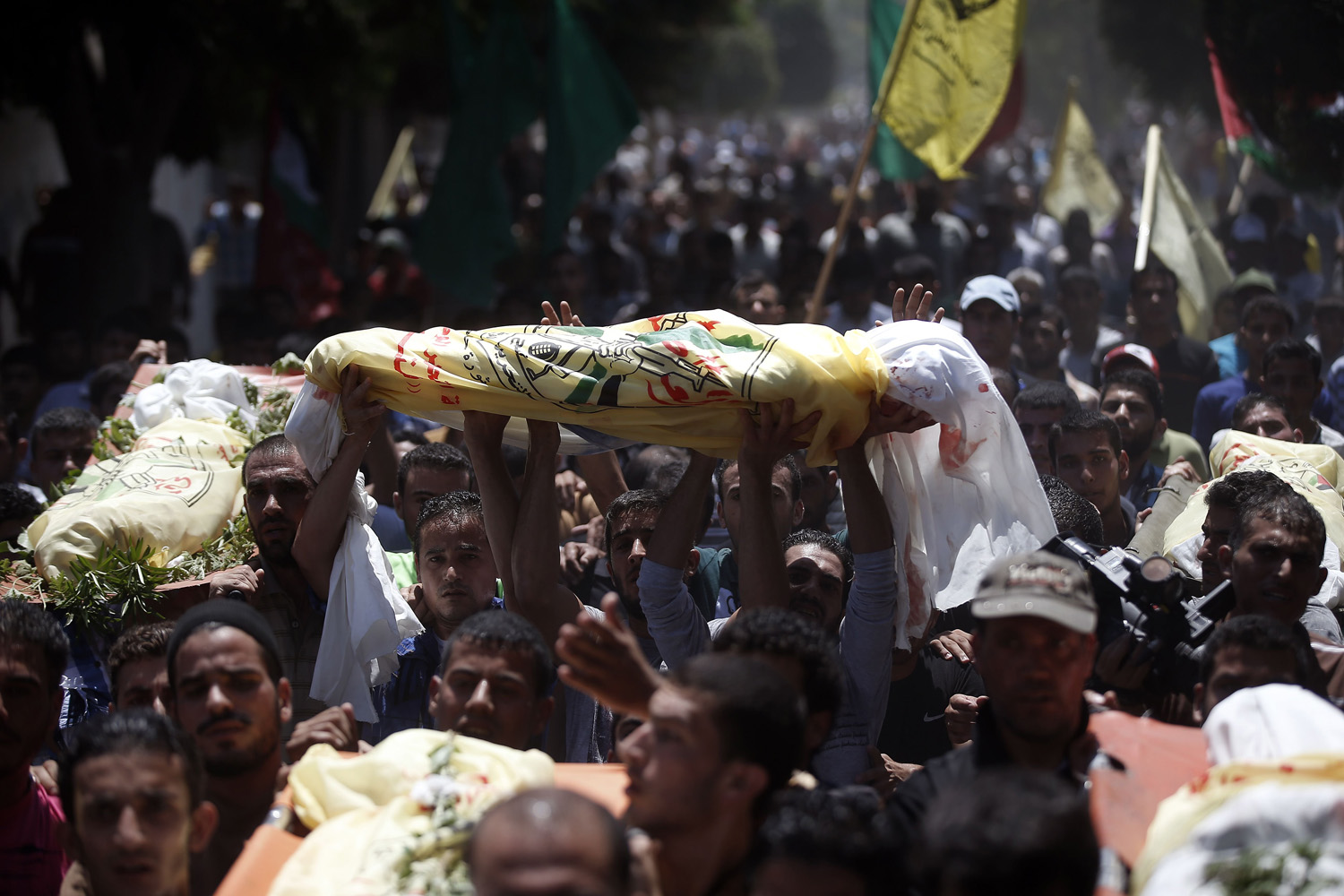 Jul. 9, 2014. Relatives and friends of the al-Kaware family carry the 7 bodies to the mosque during their funeral in Khan Yunis, in the Gaza Strip. The father, a member of the Fatah movement, and his 6 sons were all killed the day before in an Israeli air strike that targeted their home.