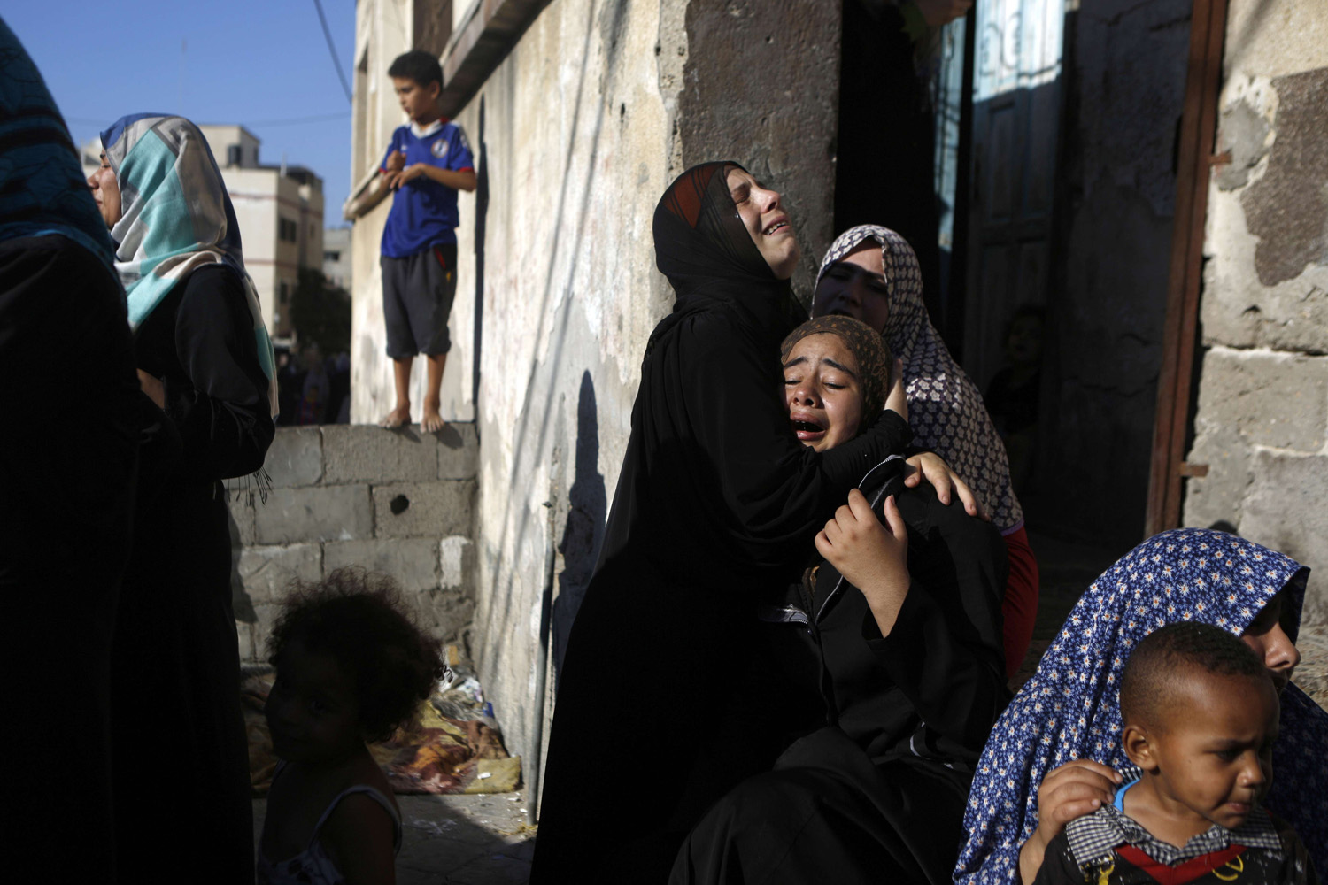 Jul. 16, 2014. Palestinian women react during the funeral of four boys, all from the Bakr family, killed during Israeli shelling, in Gaza City.