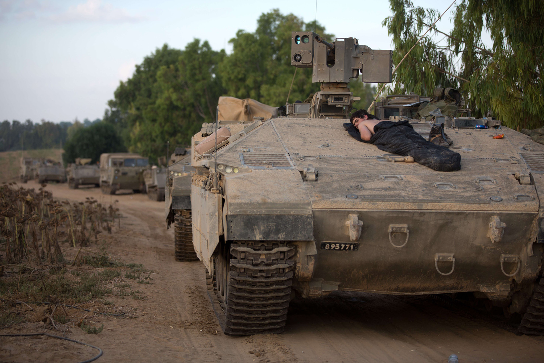 Jul. 17, 2014. An Israeli soldier sleeps on an armoured personnel carrier (APC) near the Israeli border with the Gaza Strip.