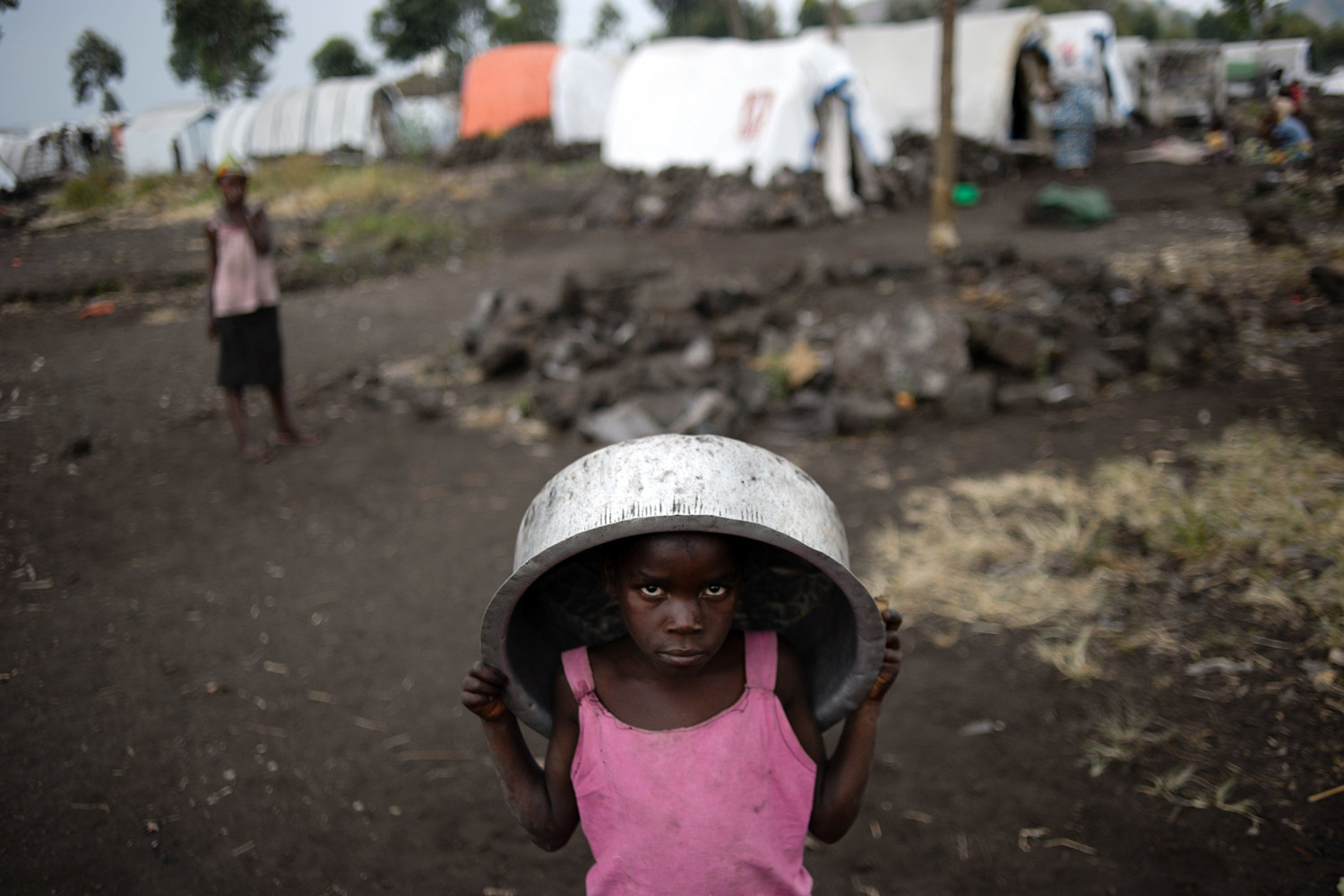 Jul. 14, 2014. A displaced Congolese child carries a basin  at the Bulengo camp for internally displaced persons (IDPs), 20 kms west of Goma in the east of the Democratic Republic of the Congo.