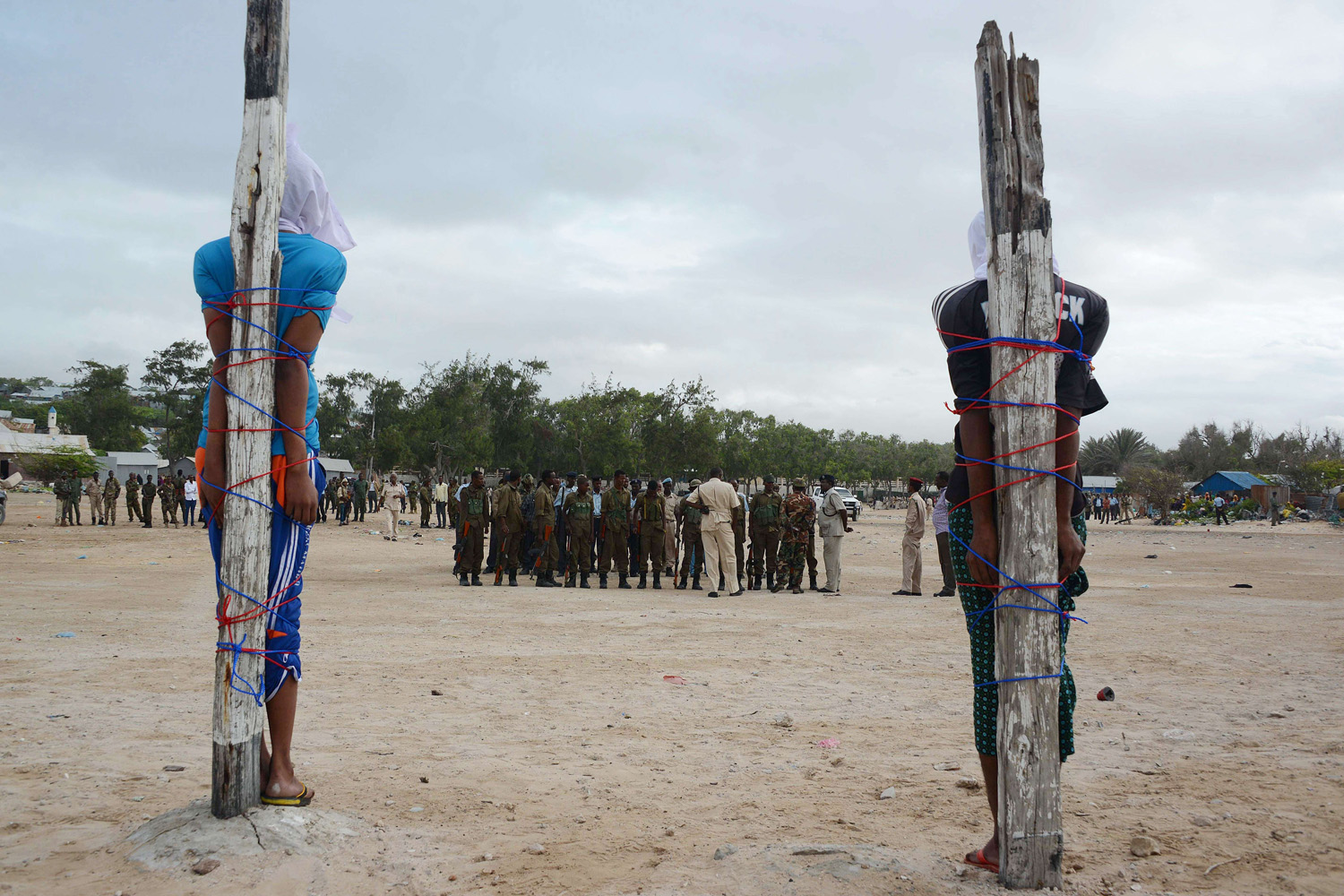 Jul. 15, 2014. Two Somalis, convicted of the murder of a Somali nurse working with a Turkish medical aid unit, are tied to large wooden stakes as they wait to be executed by a firing squad in Mogadishu.