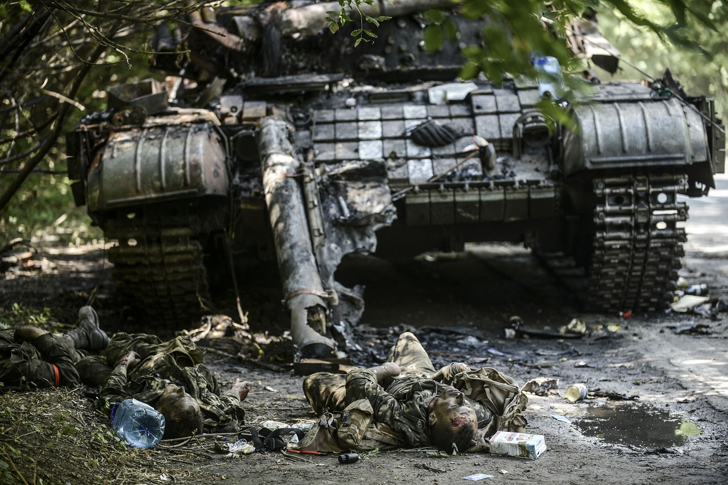 Jul. 22, 2014. Bodies of crew members lie next to a destroyed Ukrainian tank in the northern outskirts of city of Donetsk.