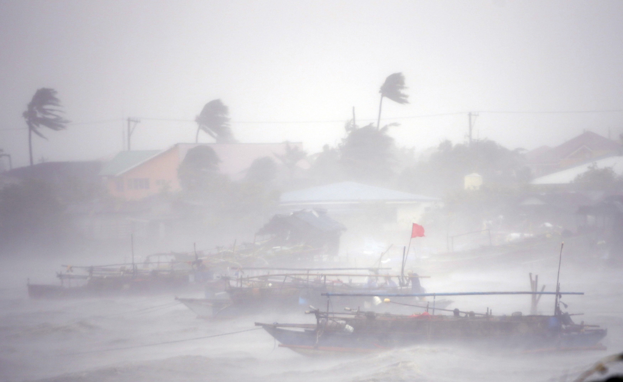 Fishing boats are pictured amid heavy winds and rain brought by Typhoon Rammasun as it hit the town of Imus, Cavite southwest of Manila, July 16, 2014.