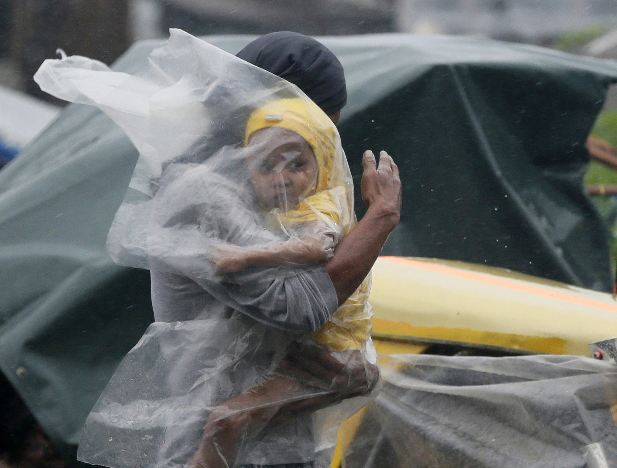 A father with his child covered under a plastic sheet flee the strong winds and rain brought by typhoon Rammasun in the Tondo slum area, in Manila, Philippines, July 16, 2014.