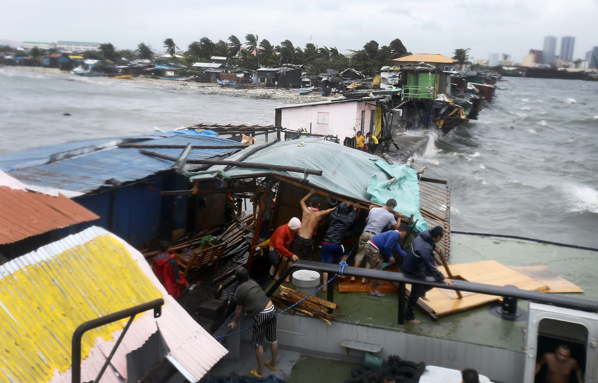 Residents dismantle a shanty  after it was damaged by a barged caused by strong winds and rain brought by typhoon Rammasun along the coastline of the Tondo slum area, in Manila, July 16, 2014.