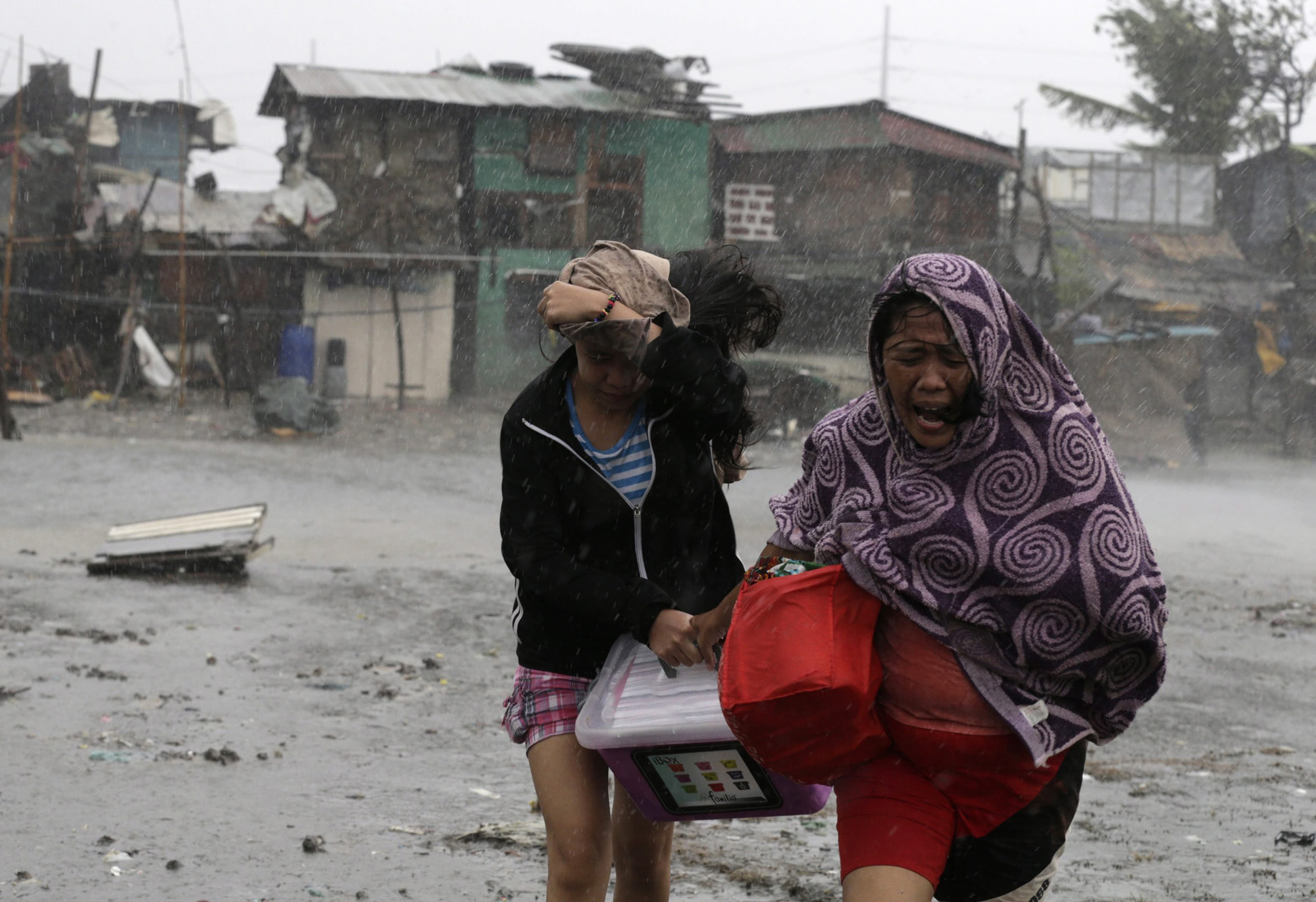 Residents flee strong winds and rain brought by typhoon Typhoon Rammasun in Las Pinas city, south of Manila, July 16, 2014.
