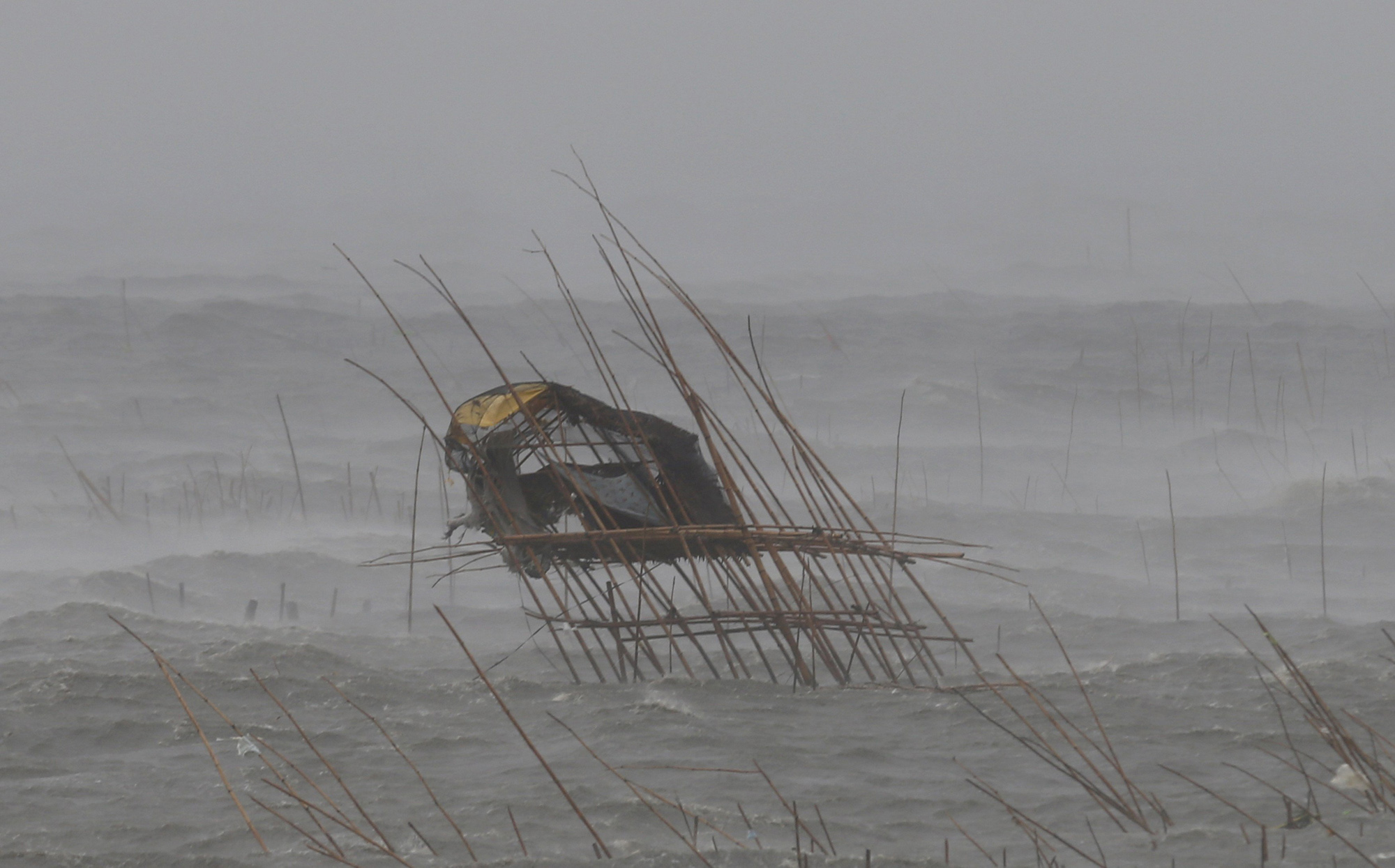 A fisherman's house in the middle of a fish pen leans to one side as it is pounded by waves, strong winds and rain brought by Typhoon Rammasun in the coastal  town of Bacoor, Cavite, southwest of Manila, July 16, 2014.
