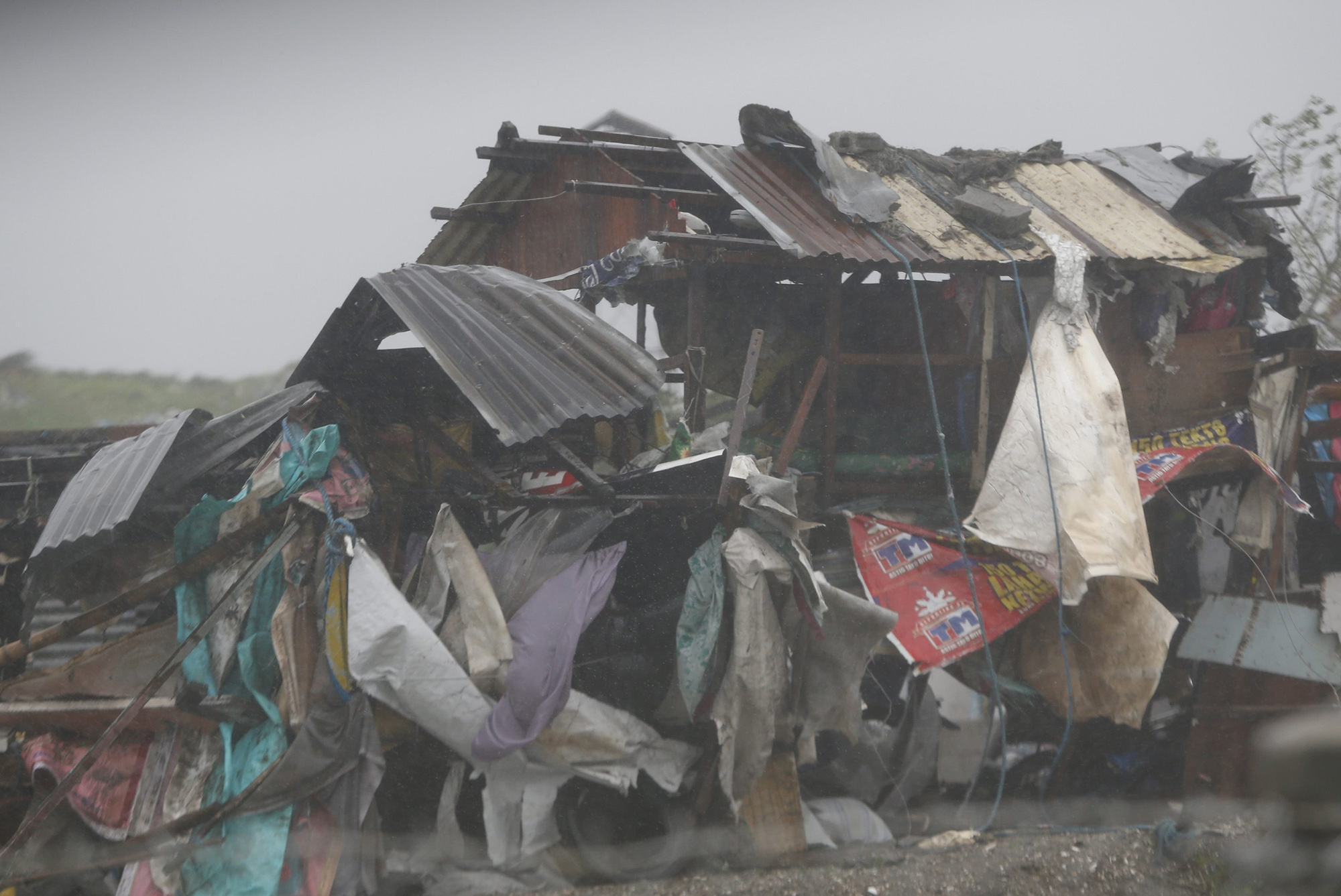 A squatter's house is pounded by strong winds and rain brought by Typhoon Rammasun as it hit the coastal town of Bacoor, Cavite southwest of Manila, July 16, 2014.