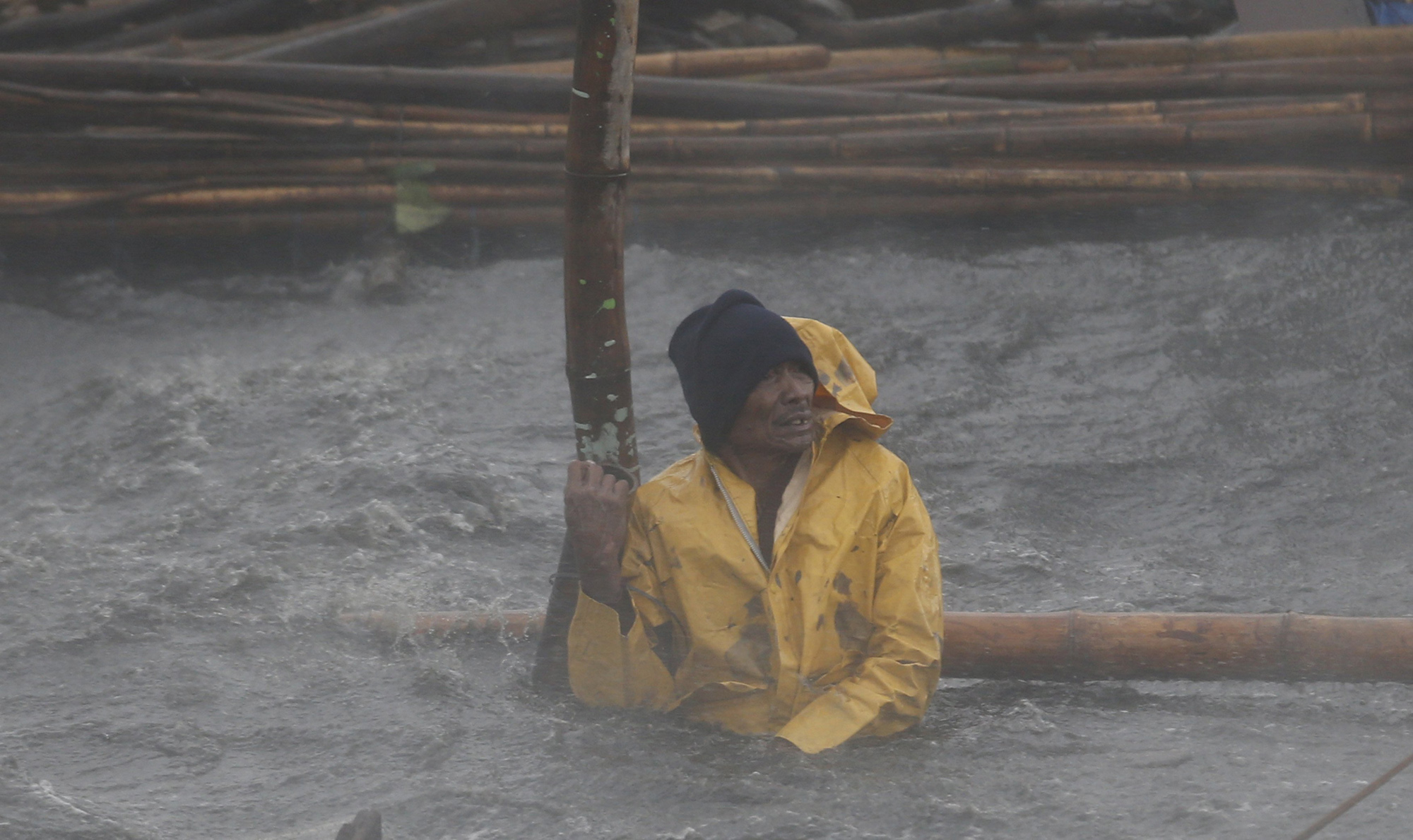 A fisherman secures his fishpen from strong winds and rain brought by Typhoon Rammasun as it hit the coastal town of Bacoor, Cavite southwest of Manila, July 16, 2014.