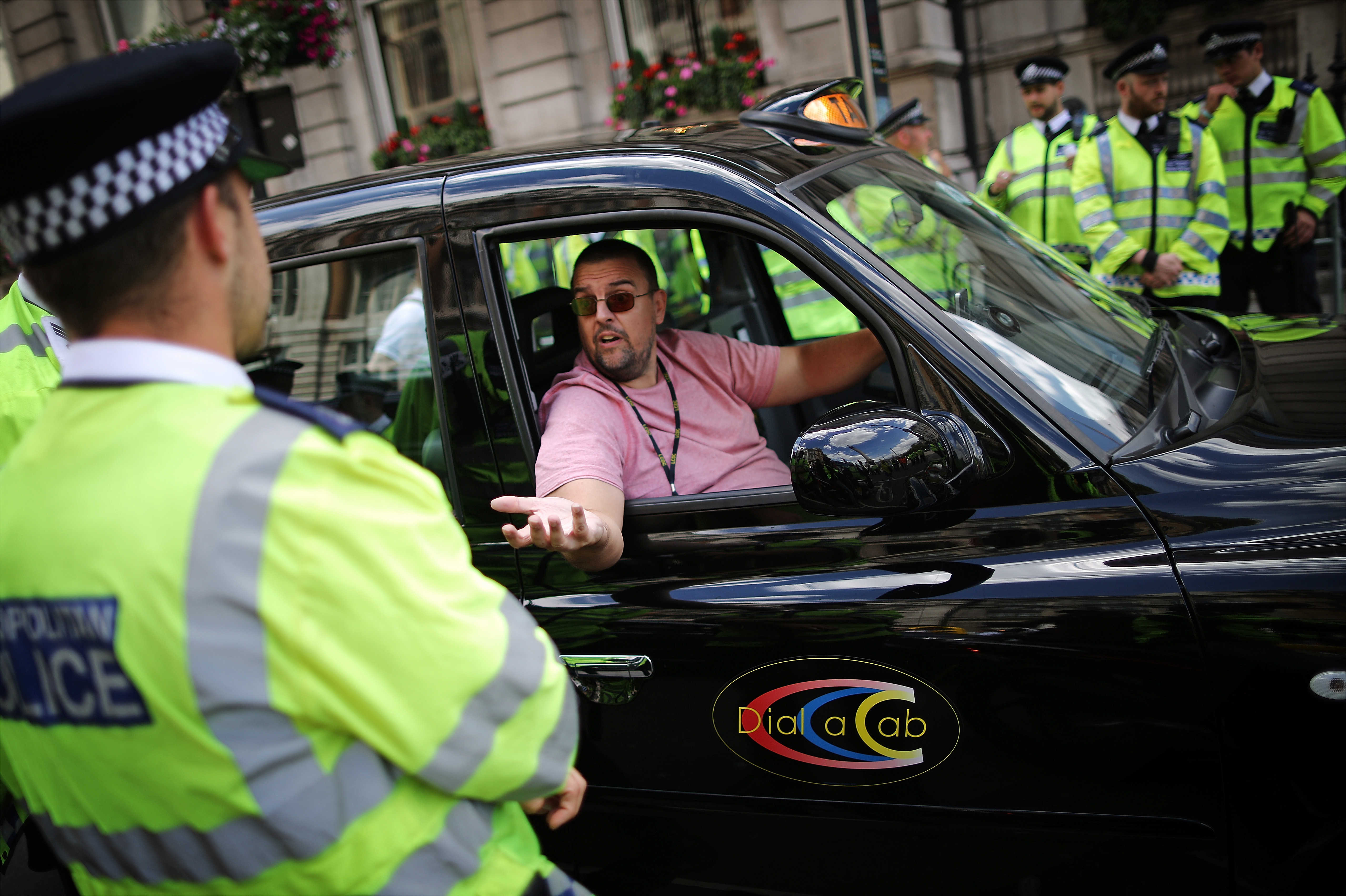 A London taxi driver speaks with Police Officers during a protest against a new smart phone app, 'Uber' on June 11, 2014 in London, England.