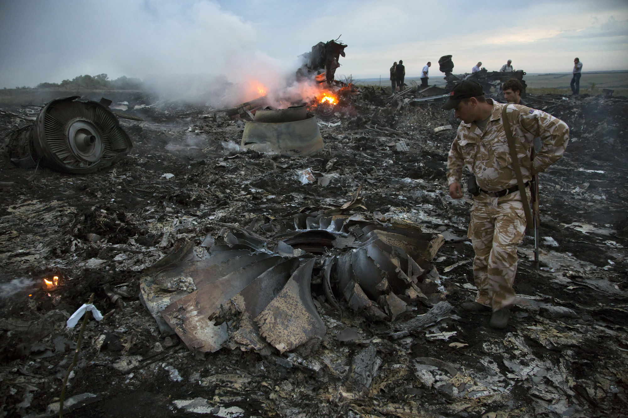 People walk amongst the debris at the crash site of a passenger plane near the village of Grabovo, Ukraine, July 17, 2014.