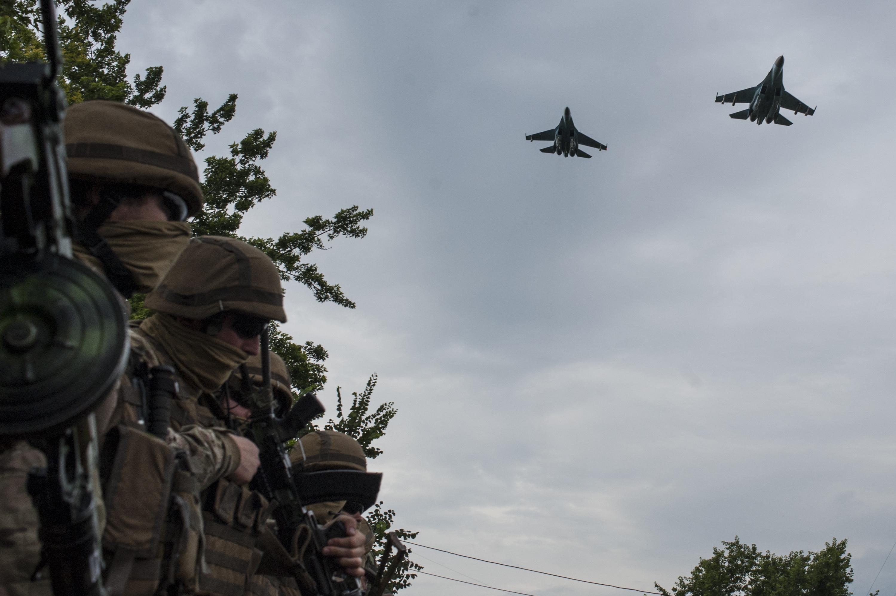 Ukrainian Army jets fly over the Ukrainian government military base while troops wait for Ukrainian President Petro Poroshenko's visit in Devhenke village, Kharkiv region, eastern Ukraine on July 8, 2014.