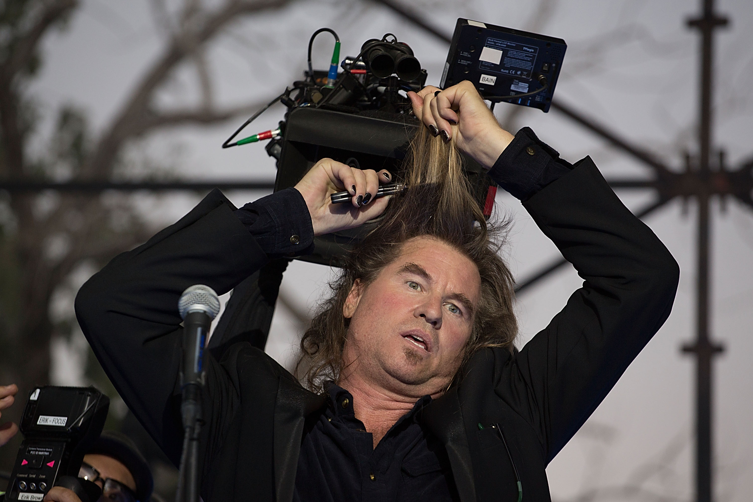 Actor Val Kilmer cuts his hair off on stage while filming the new Terrence Malick movie during day one of Fun Fun Fun Fest at Auditorium Shores on November 2, 2012 in Austin, Texas.
