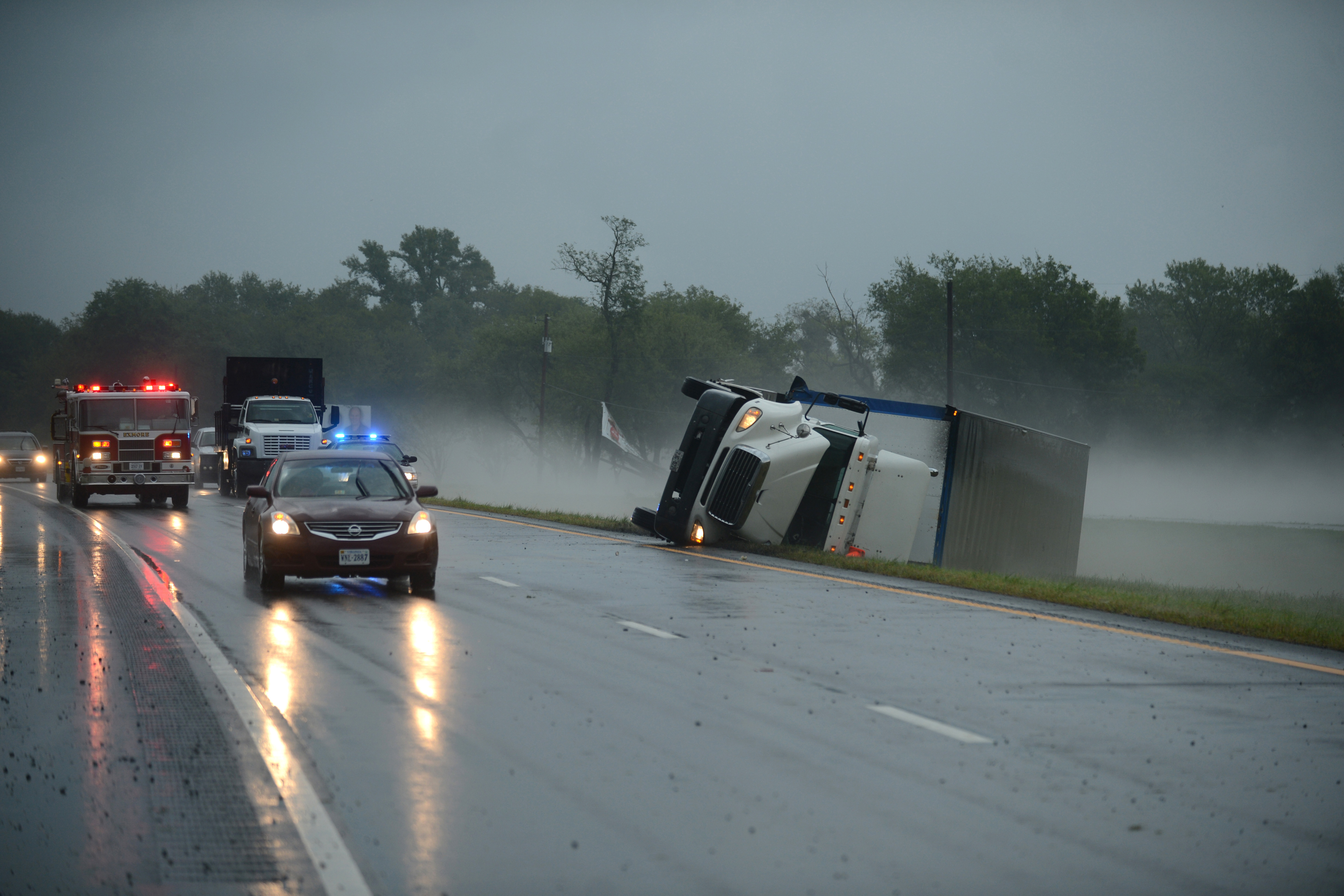 A tractor trailer truck lies on its side in the median of U.S. Route 13 while a fire engine responds to a nearby campground after a severe storm passed through the area, Cheriton, Va, July 24, 2014.