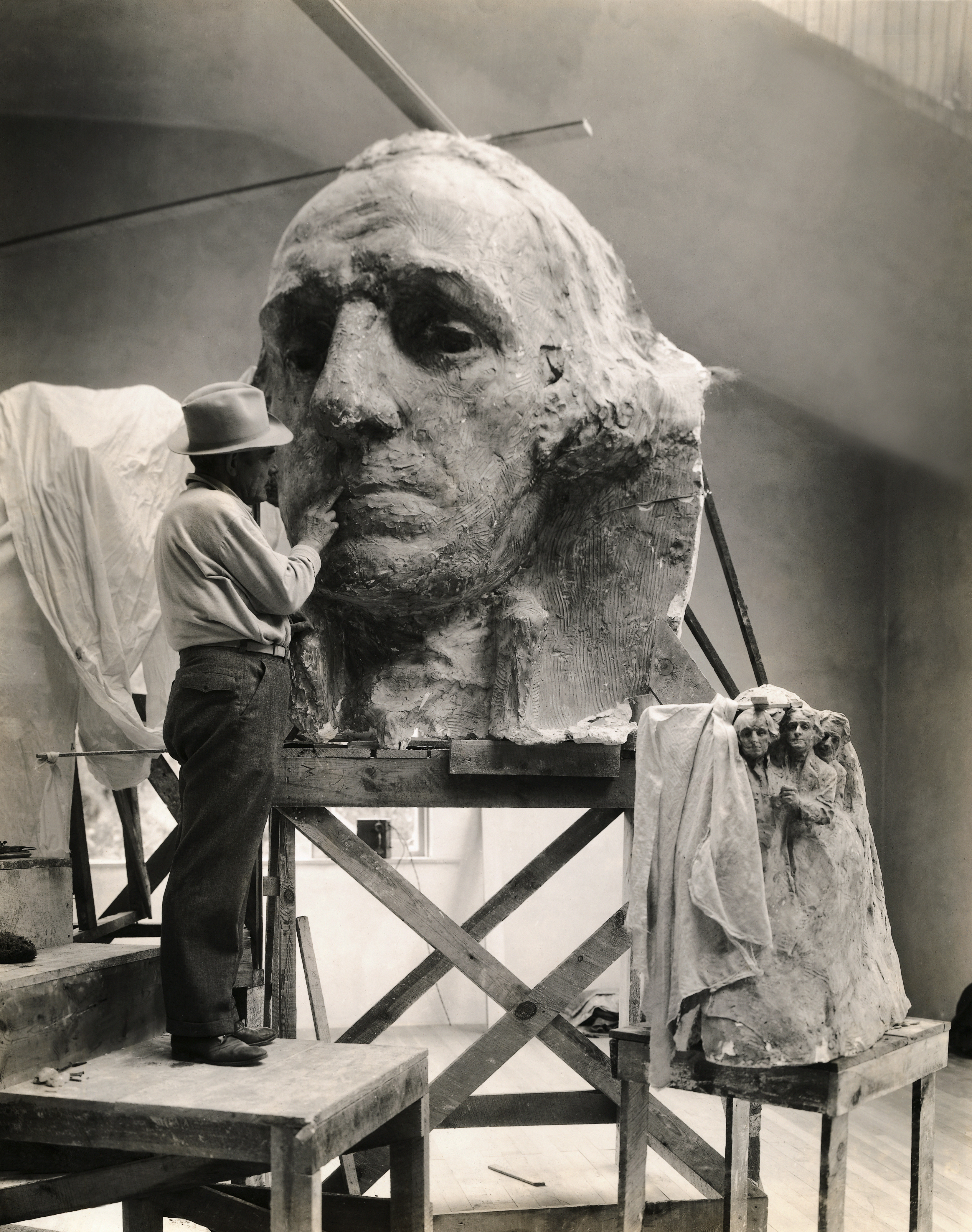 Gutzon Borglum seen in his studio at Rushmore is working on the model of the head of Washington, Black Hills area of Keystone, S.D., circa 1930s.