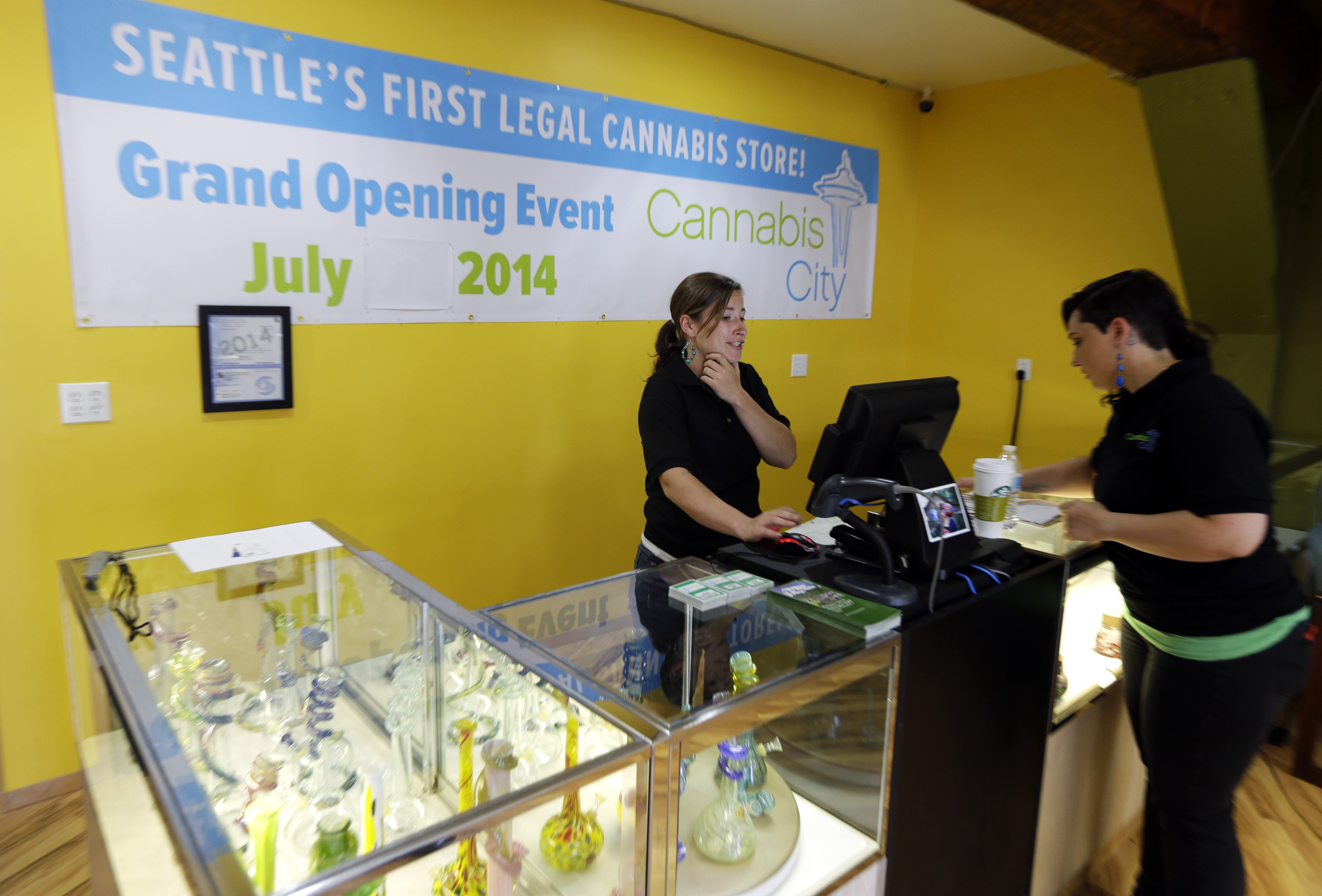 Amber McGowan, right, and Krystal Klacsan, left, work in the cash register area at the recreational marijuana store Cannabis City in Seattle on July 7, 2014.