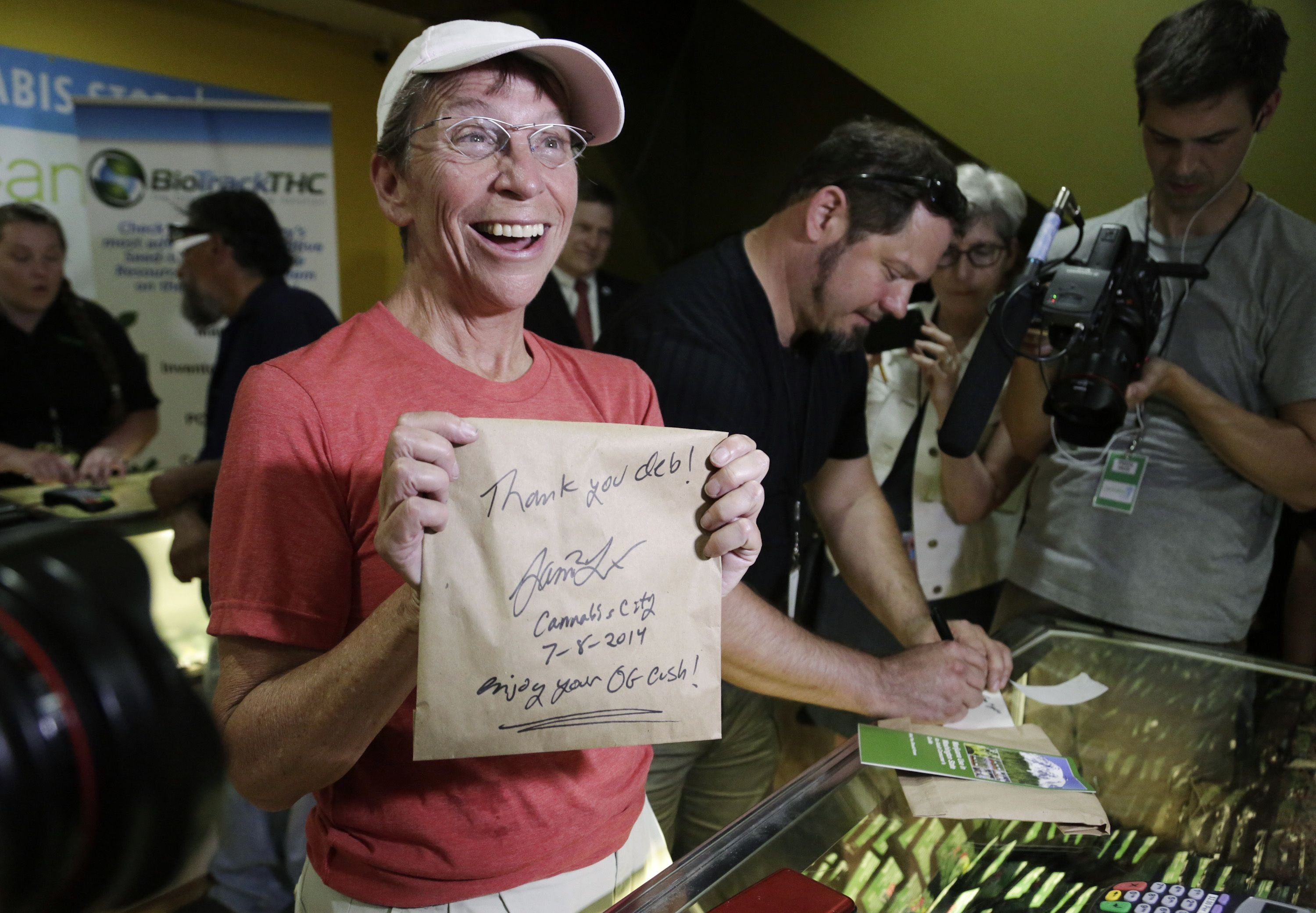 Deb Greene, the first customer at Cannabis City, holds up her purchase signed by owner James Lathrop during the first day of legal retail marijuana sales in Seattle on July 8, 2014.