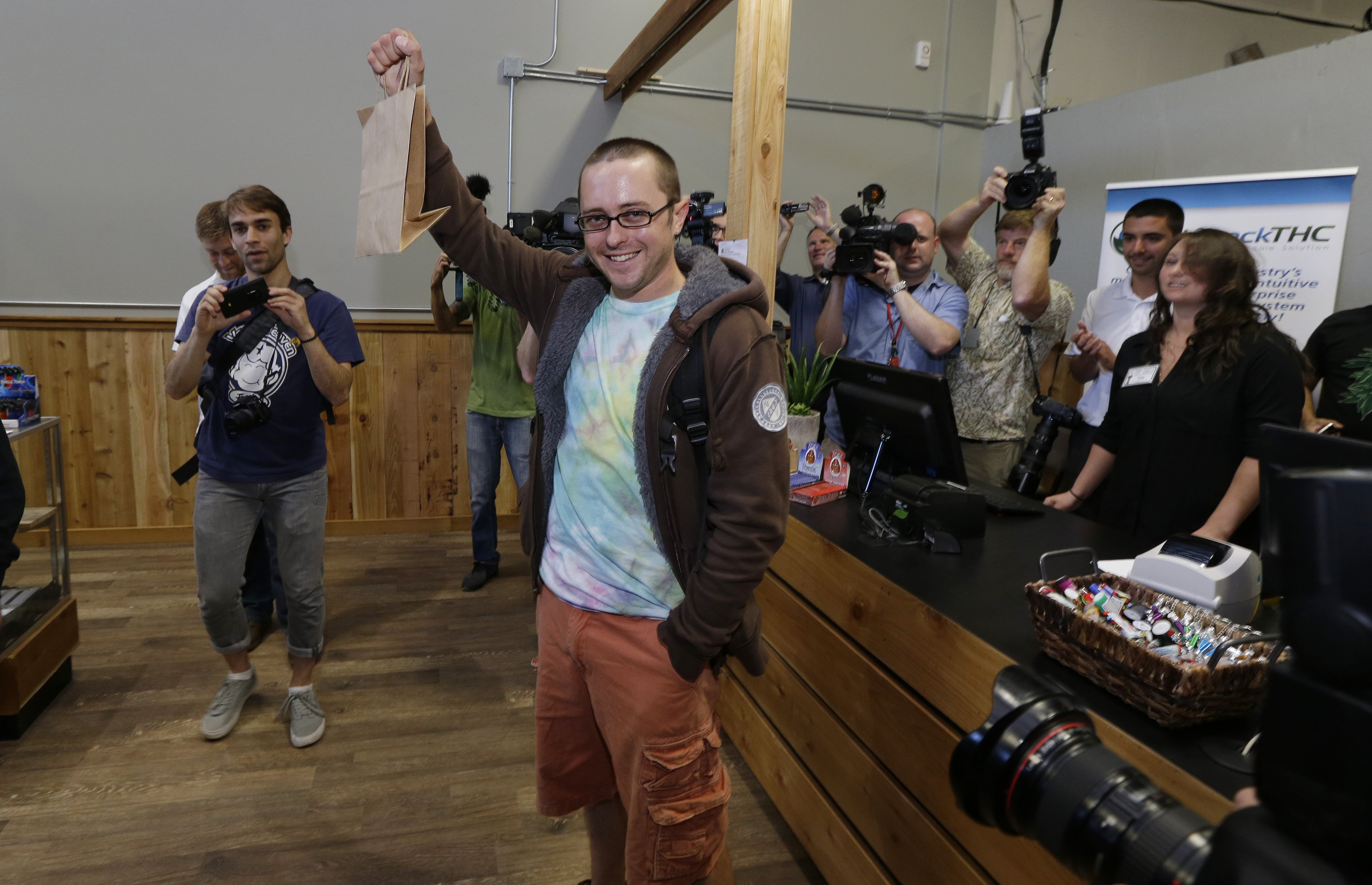 Cale Holdsworth, of Abeline, Kan., who waited in line since 4:00 am, holds up his purchase after being the first in line to buy legal recreational marijuana at Top Shelf Cannabis in Bellingham, Wash. on July 8, 2014.