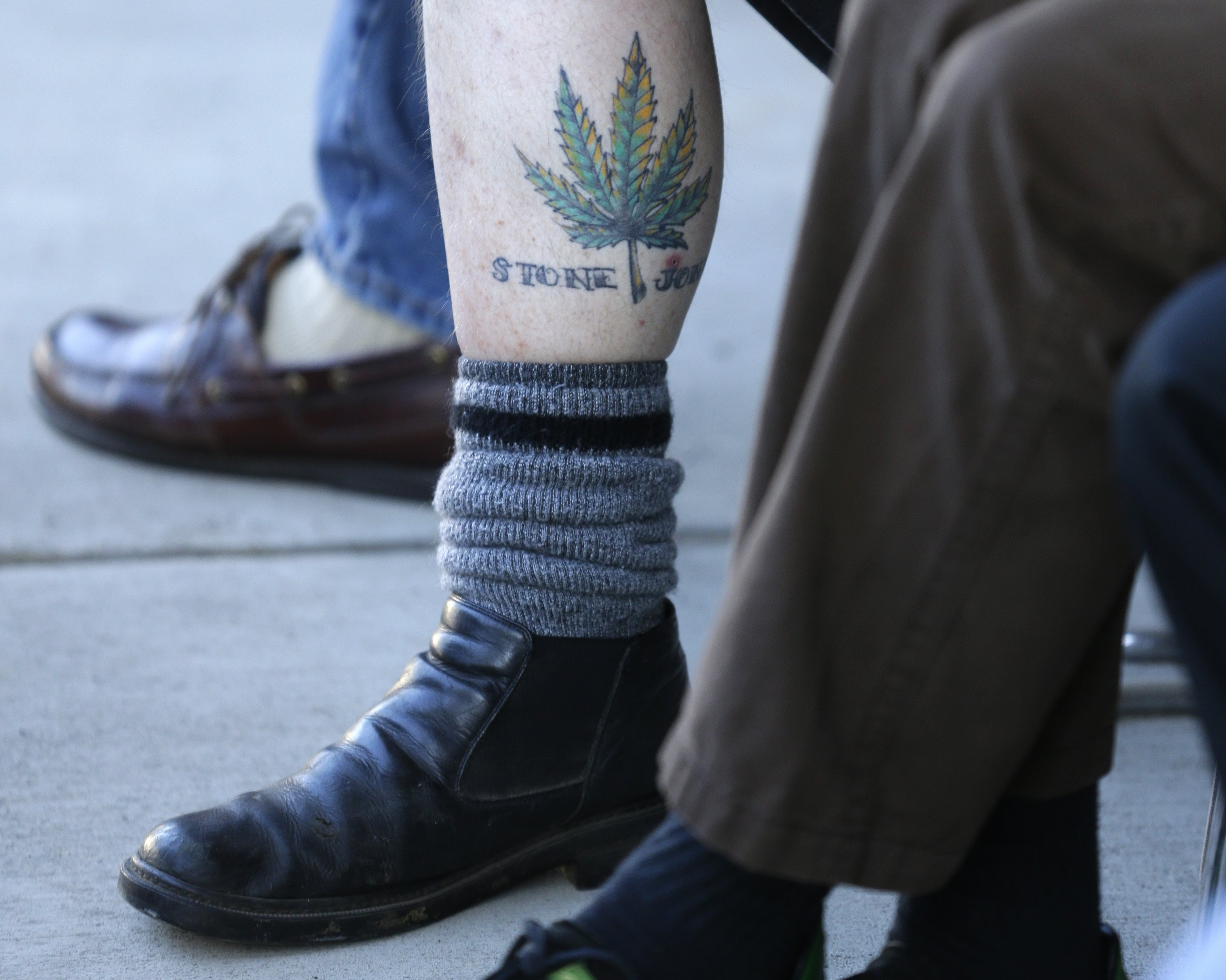 A man waiting in line to buy recreational marijuana displays his pot-leaf tattoo oustside of Top Shelf Cannabis in Bellingham, Wash. on July 8, 2014.