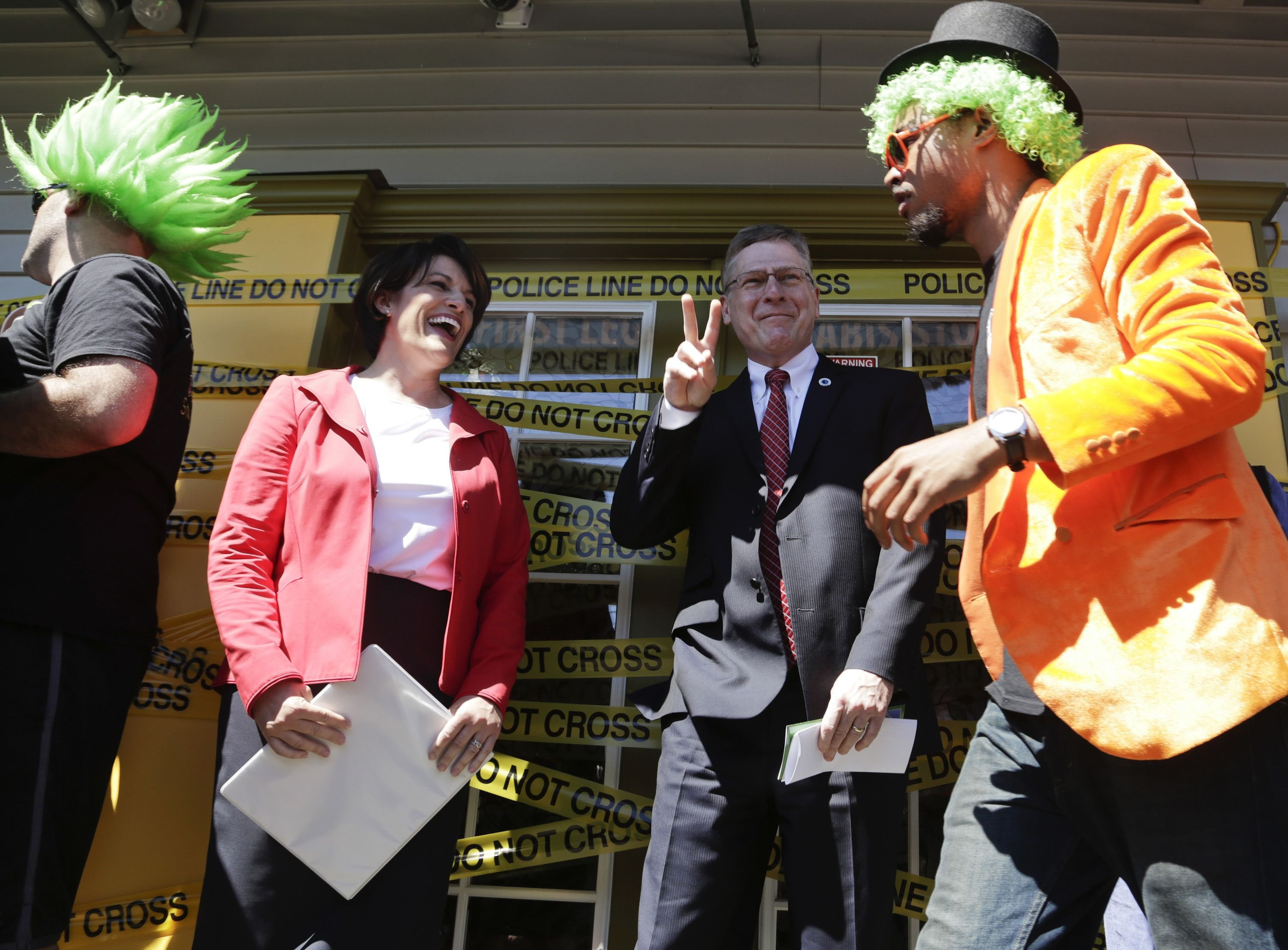 Alison Holcomb (2nd L), Criminal Justice Director of ACLU of Washington State and co-author of state Initiative 502 legalizing marijuana, and Seattle City Attorney Pete Holmes (2nd R) take part in the opening ceremonies at Cannabis City during the first day of legal retail marijuana sales in Seattle on July 8, 2014.