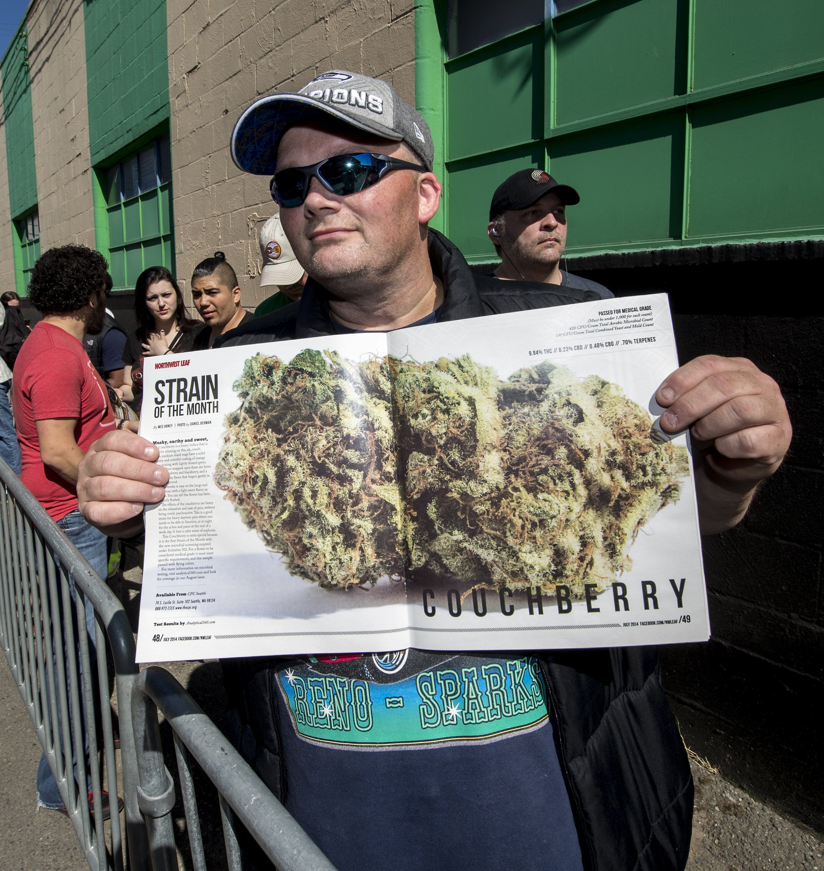 Allan Ridge shows off the centerfold of Northwest Leaf while waiting in line at Cannabis City in Seattle on July 8, 2014.