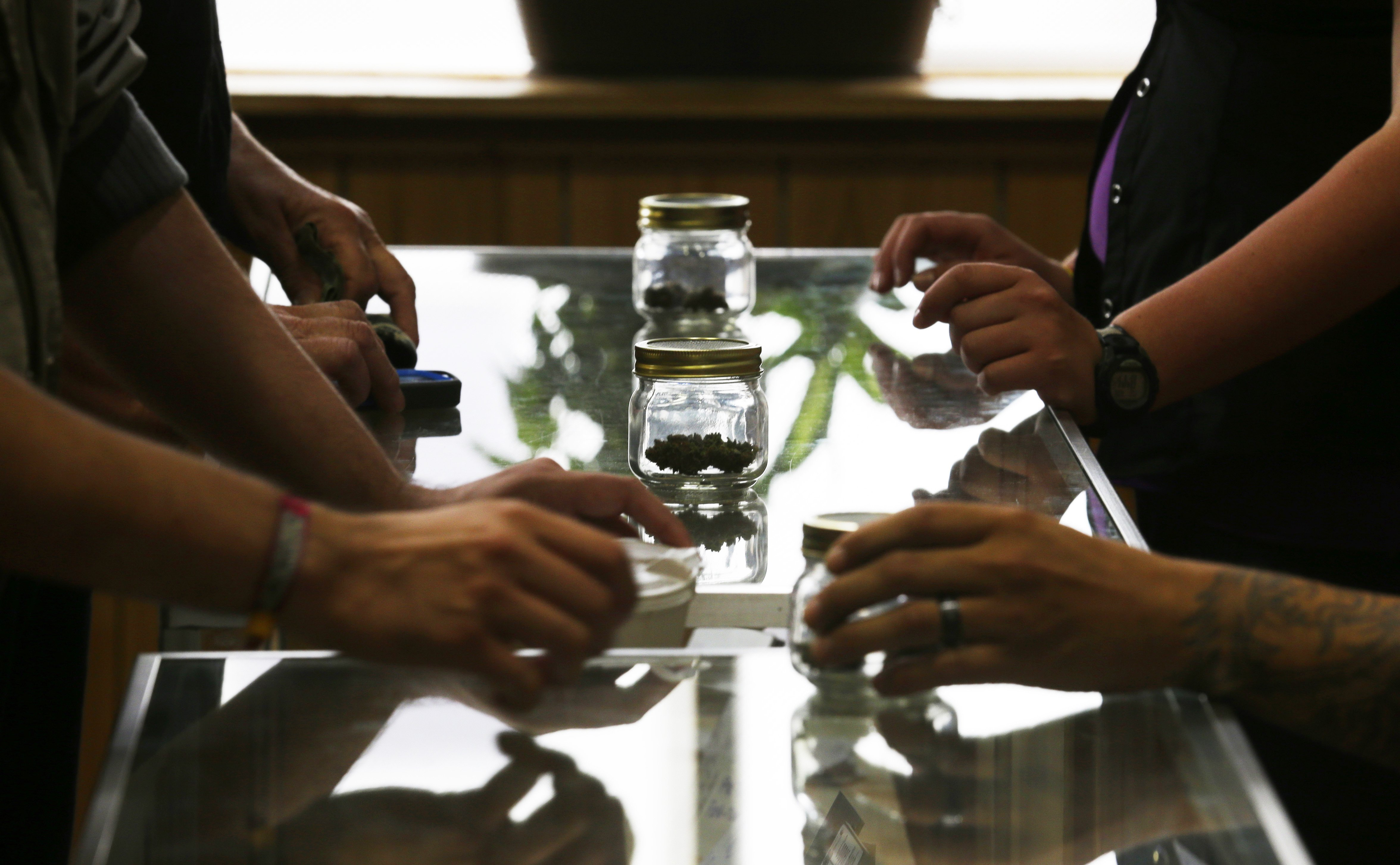 """Customers on the left and sales clerks on the right pass """"sniff jars"""" back and forth on a glass countertop as they discuss different strains of recreational marijuana at Top Shelf Cannabis in Bellingham, Wash. on July 8, 2014."""