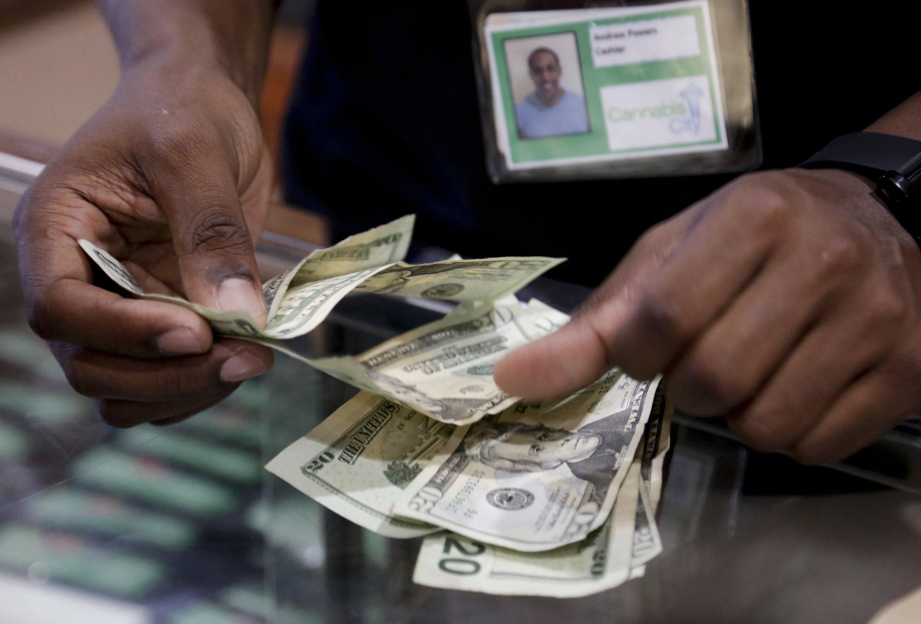 Cashier Andrew Powers completes a cash marijuana purchase at Cannabis City during the first day of legal retail marijuana sales in Seattle on July 8, 2014.
