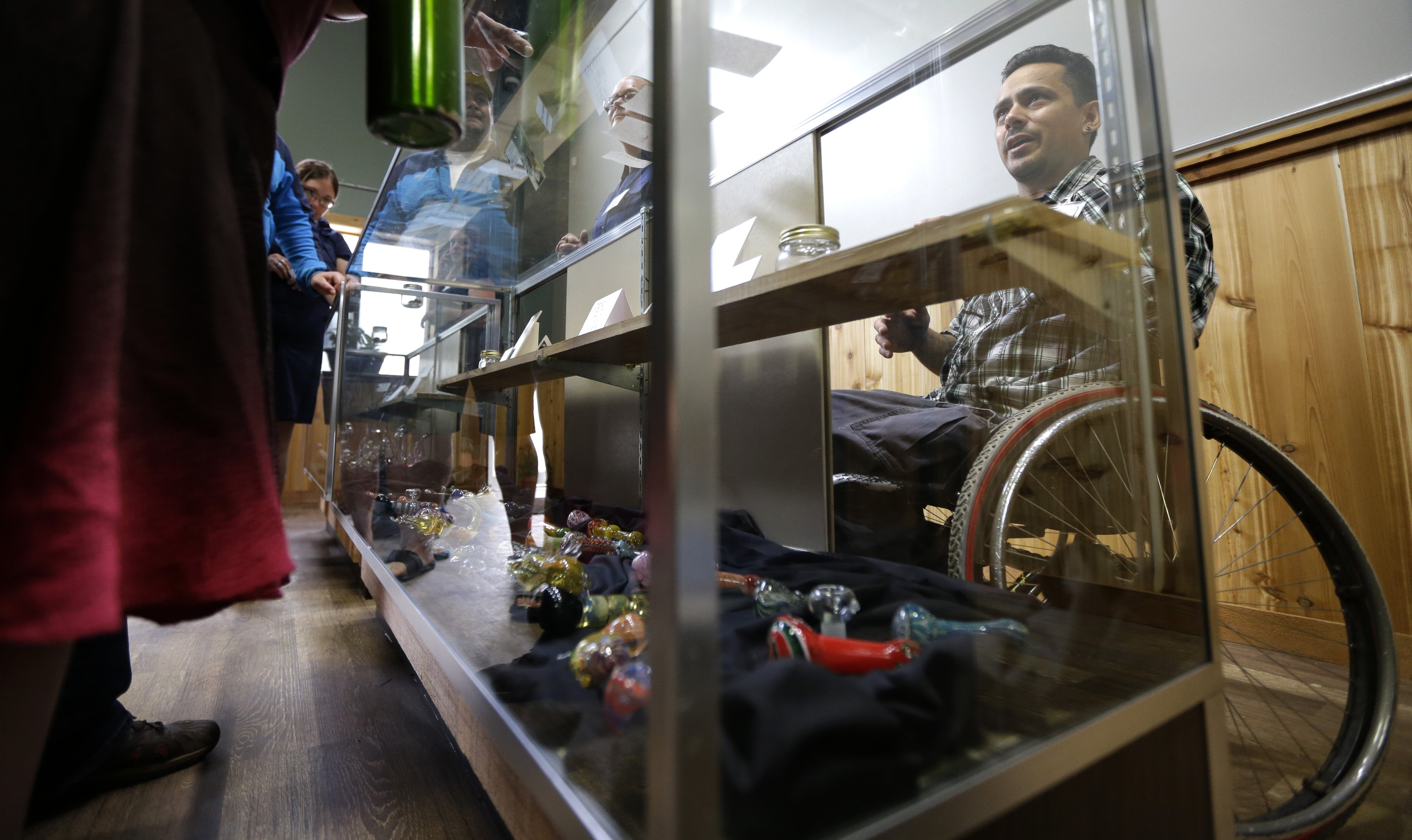 Jeremy Hunter, right, an employee at Top Shelf Cannabis talks about different strains of marijuana as he works behind a case displaying glass pipes in Bellingham, Wash. on July 8, 2014.