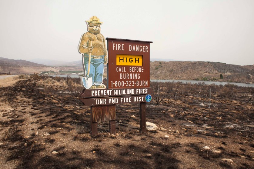 A sign surrounded by scorched earth warns drivers of the high fire danger along US State Route 97 after it was hit by the Carlton Complex fire near Pateros