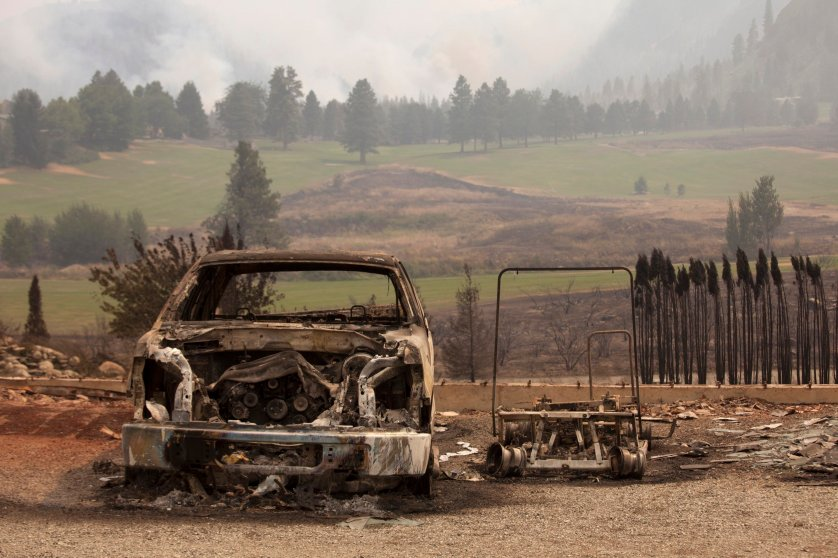 A damaged vehicle is pictured near Alta Lake Golf Course after it was consumed by the Carlton Complex Fire, which can be seen burning in the distance, near Pateros