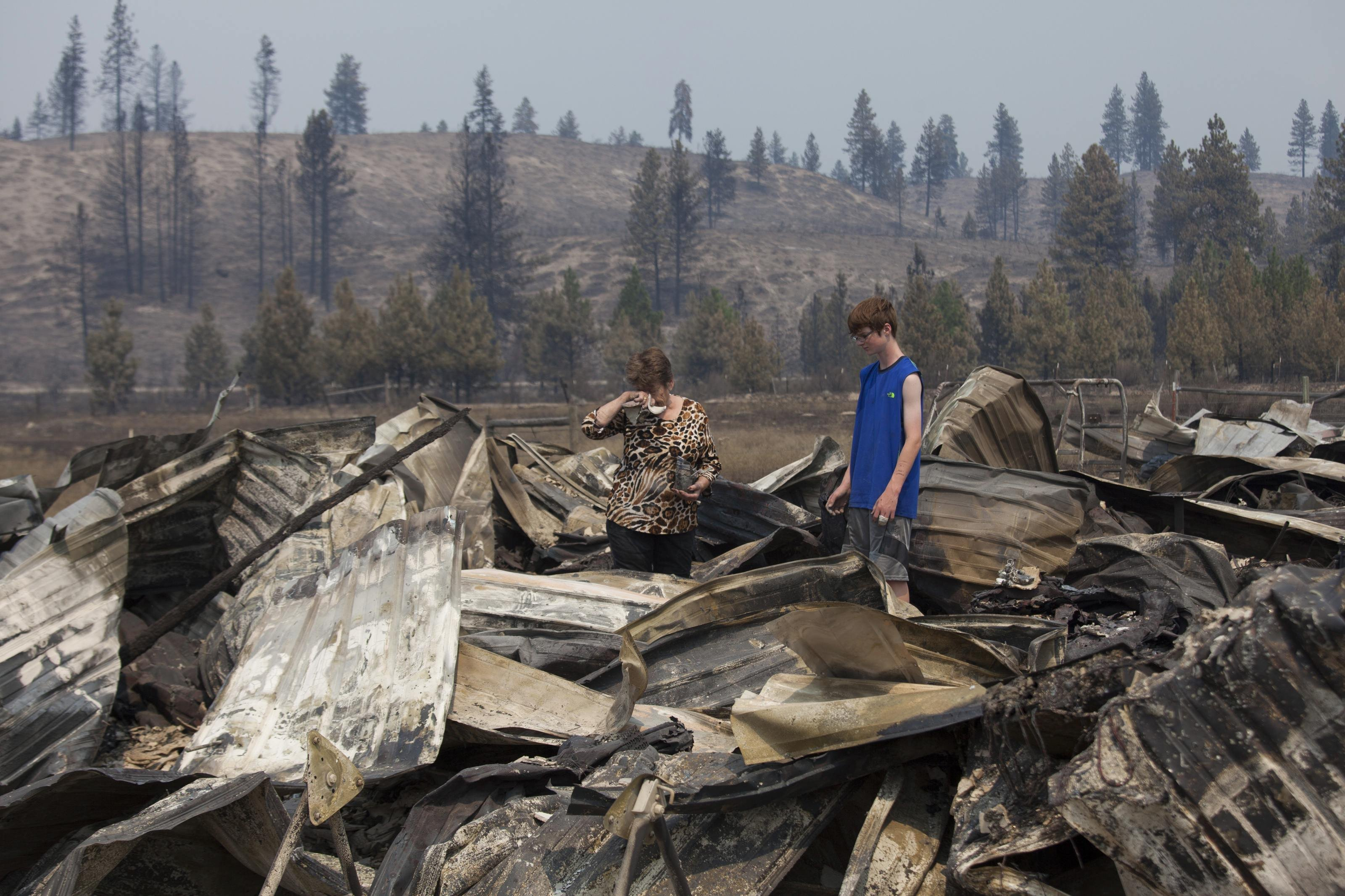 Mim Morris  wipes her forehead as she looks through the remnants of her home, which was destroyed by the Carlton Complex Fire, as her grandson, Joel Lafer, 14, joins her near Malott, Washington on July 20, 2014.