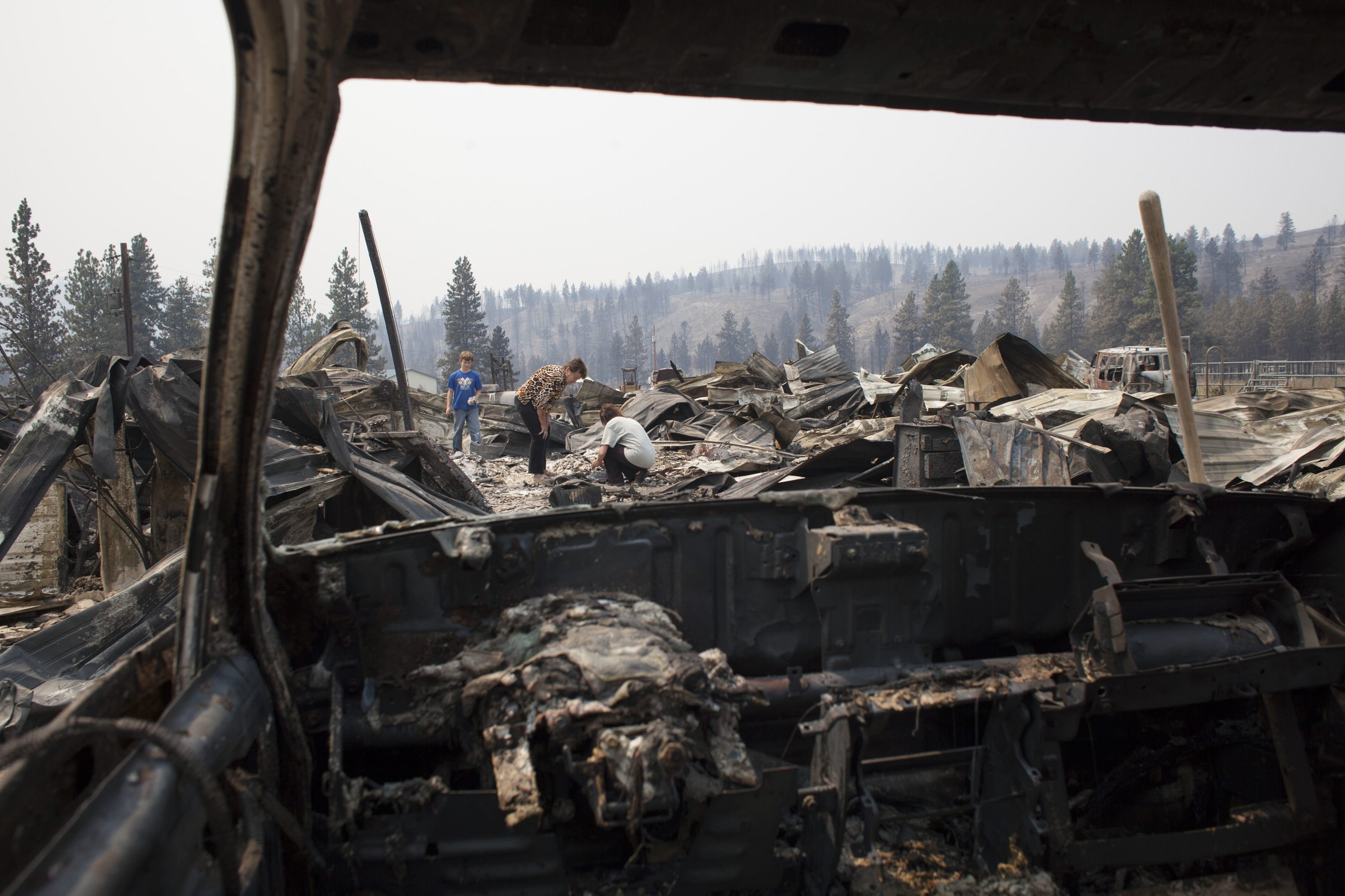 Seen through the windshield of a burnt vehicle, Mim Morris (C) looks through the remnants of her home, which was destroyed by the Carlton Complex Fire, as her grandson, Sean Lafer (L), 12 , and daughter, Laura Lafer (R), join her near Malott, Washington on July 20, 2014.