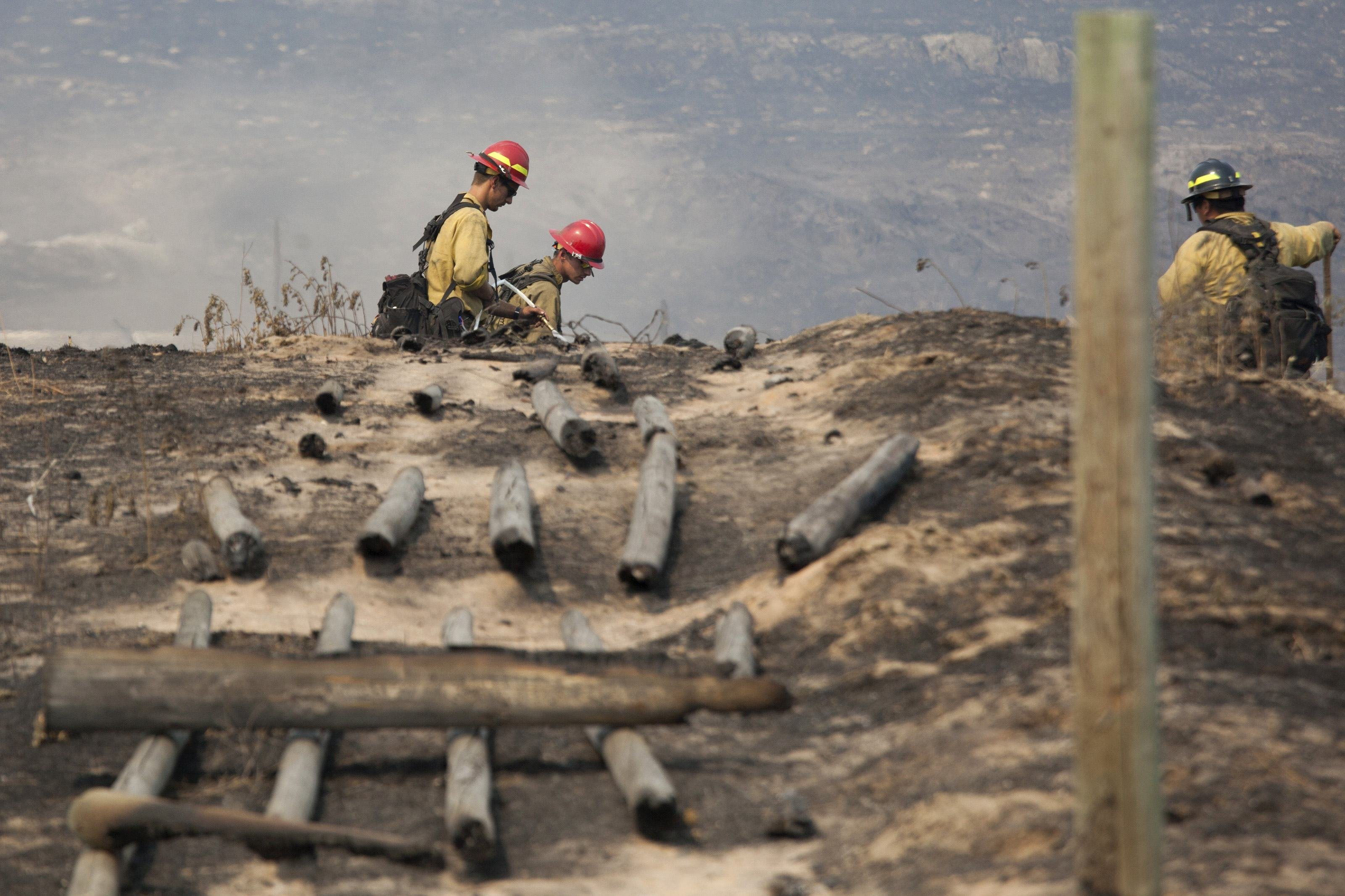 Firefighters work in a field near a burnt fence that was hit by the Carlton Complex Fire near Brewster, Washington on July 20, 2014.