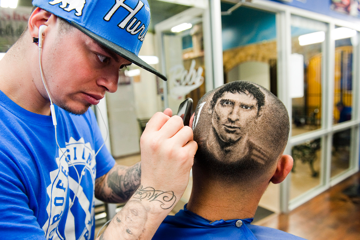 A likeness of Argentine soccer player Lionel Messi is cut onto the head of a customer ahead of the World Cup match between Argentina and Switzerland.
