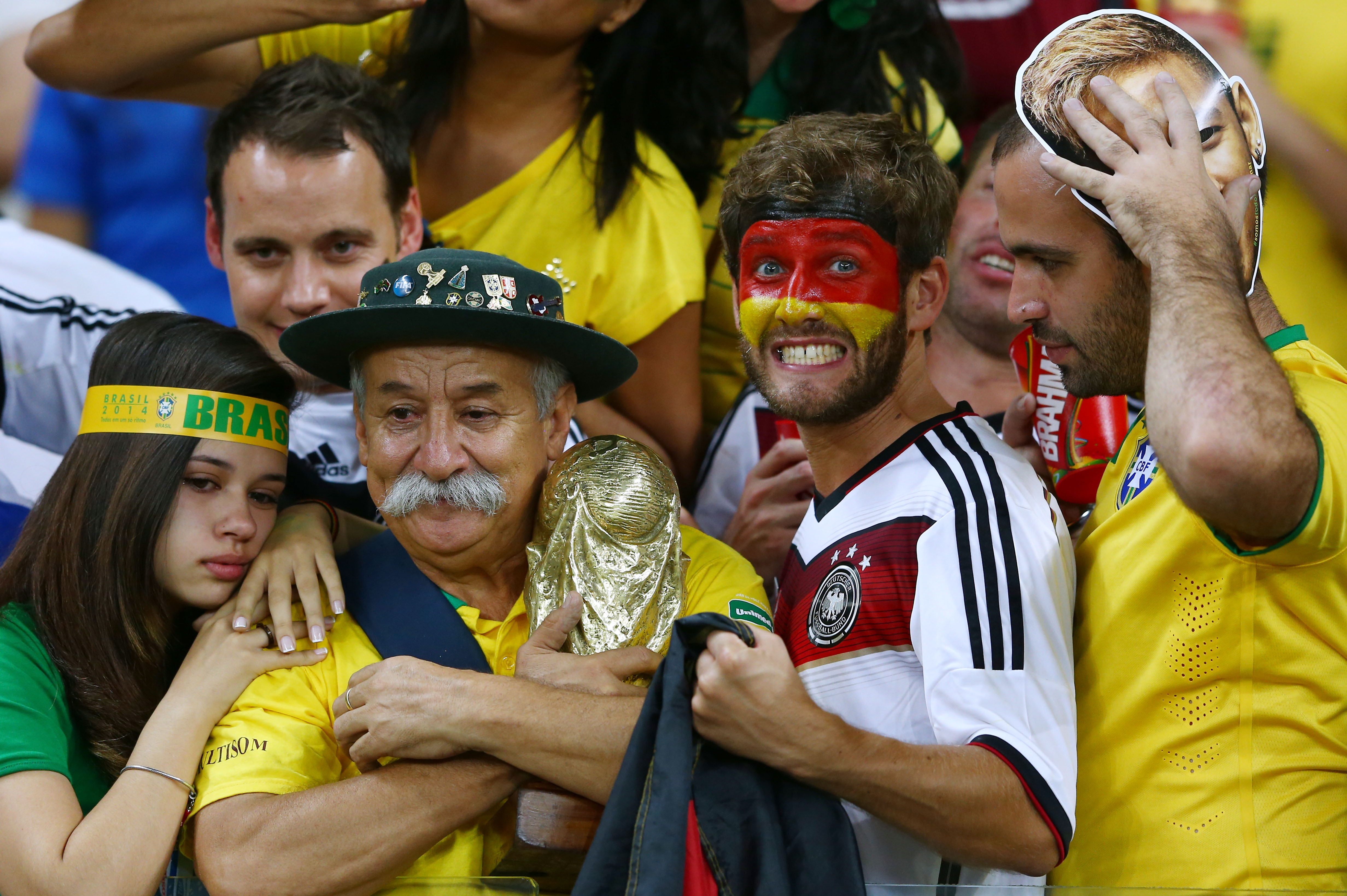 A Germany fan reacts while surrounded by dejected Brazil fans after Germany's 7-1 win during the 2014 FIFA World Cup Brazil Semi Final match between Brazil and Germany at Estadio Mineirao on July 8, 2014 in Belo Horizonte, Brazil.