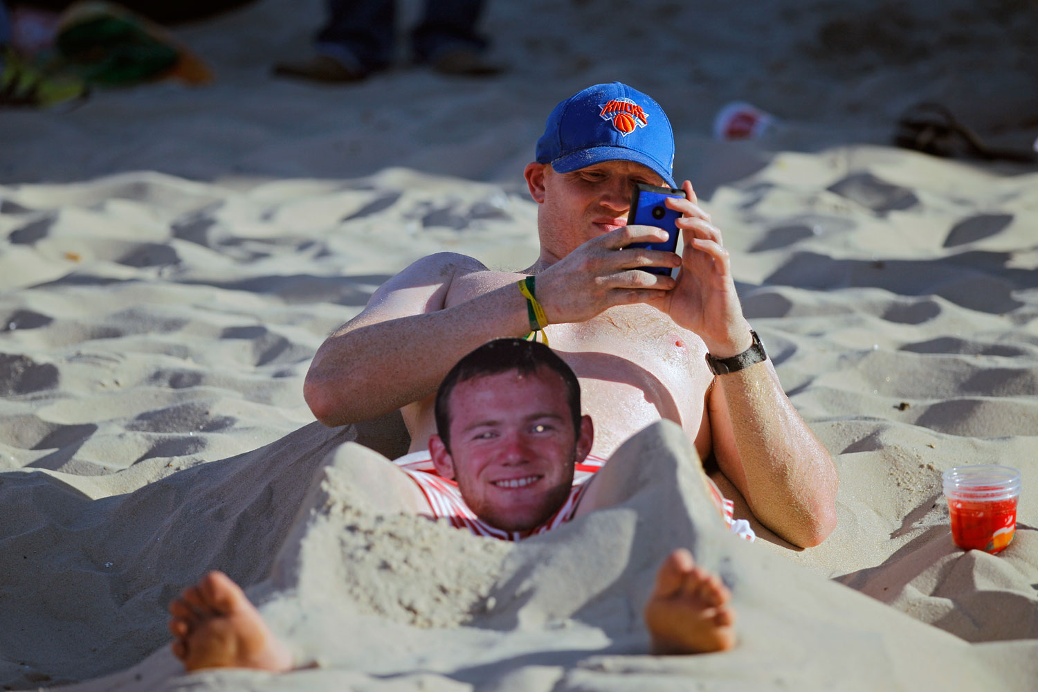 An England fan lies on the sand of Copacabana beach with a mask of English soccer star Wayne Rooney between his legs, in Rio de Janeiro on June 14, 2014.