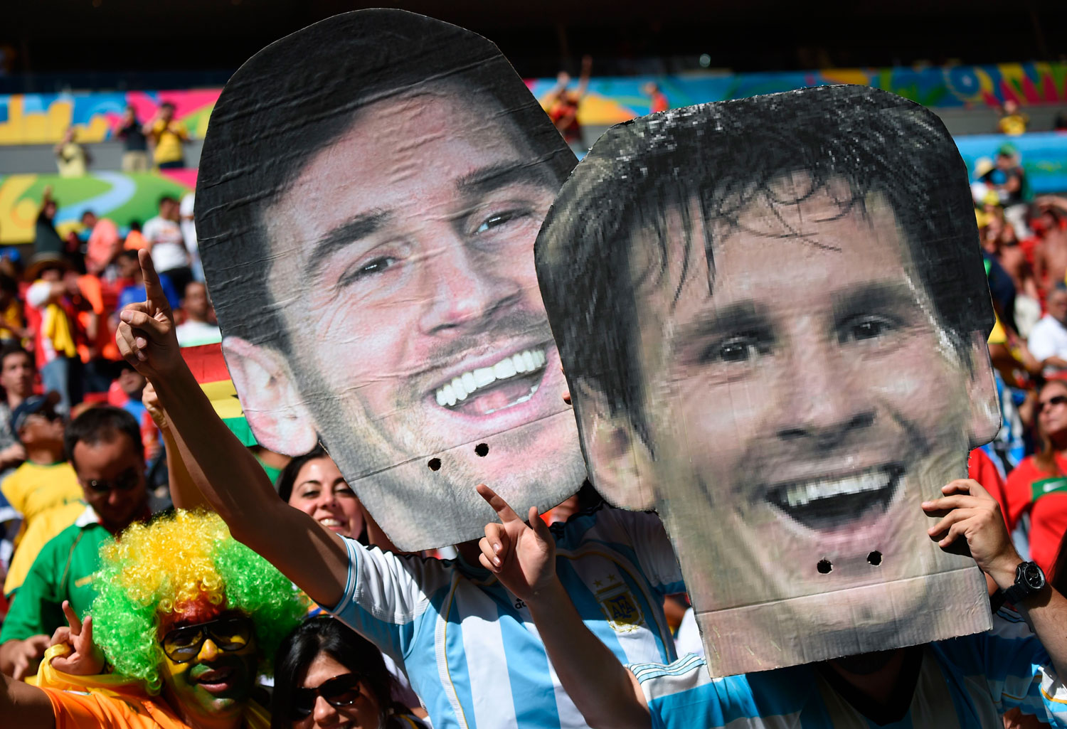 Argentina fans hold up portraits of Argentinian player Lionel Messi during the match between Portugal and Ghana at the Mane Garrincha National Stadium in Brasilia, Brazil on June 26, 2014.