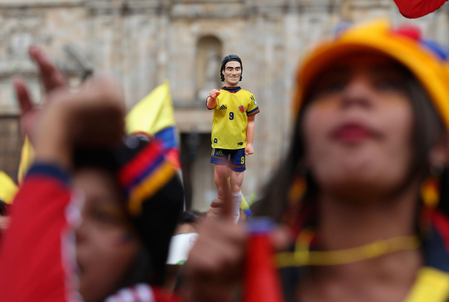 Colombia's fans hold a toy figurine of Colombia's national soccer player Falcao as they watch a broadcast of the game between Colombia and Uruguay, at Bolivar Square in Bogota on June 28, 2014.