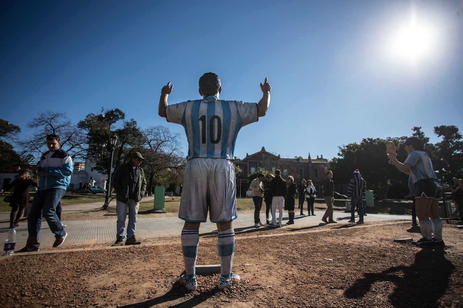 Tourists walk past sculptures of Argentinean players Diego Maradona and player Lionel Messi of Argentina's national soccer team, in the Intendant Alvear Square in Buenos Aires, Argentina on June 19, 2014.